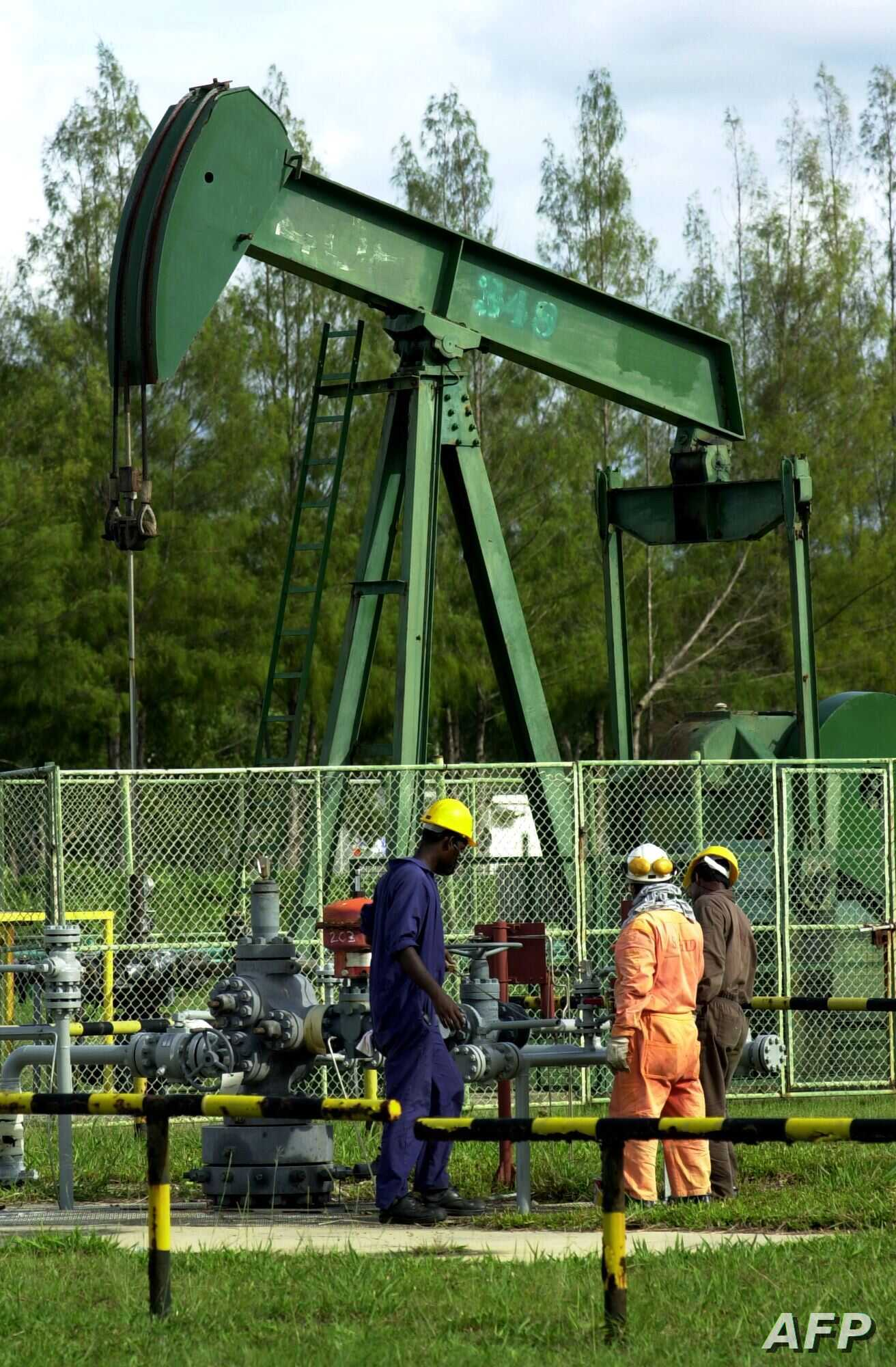 FILE - Workers working in front of one of the Bruneian Shell's oil well pumps in Seria, Brunei, Nov. 16, 2000.