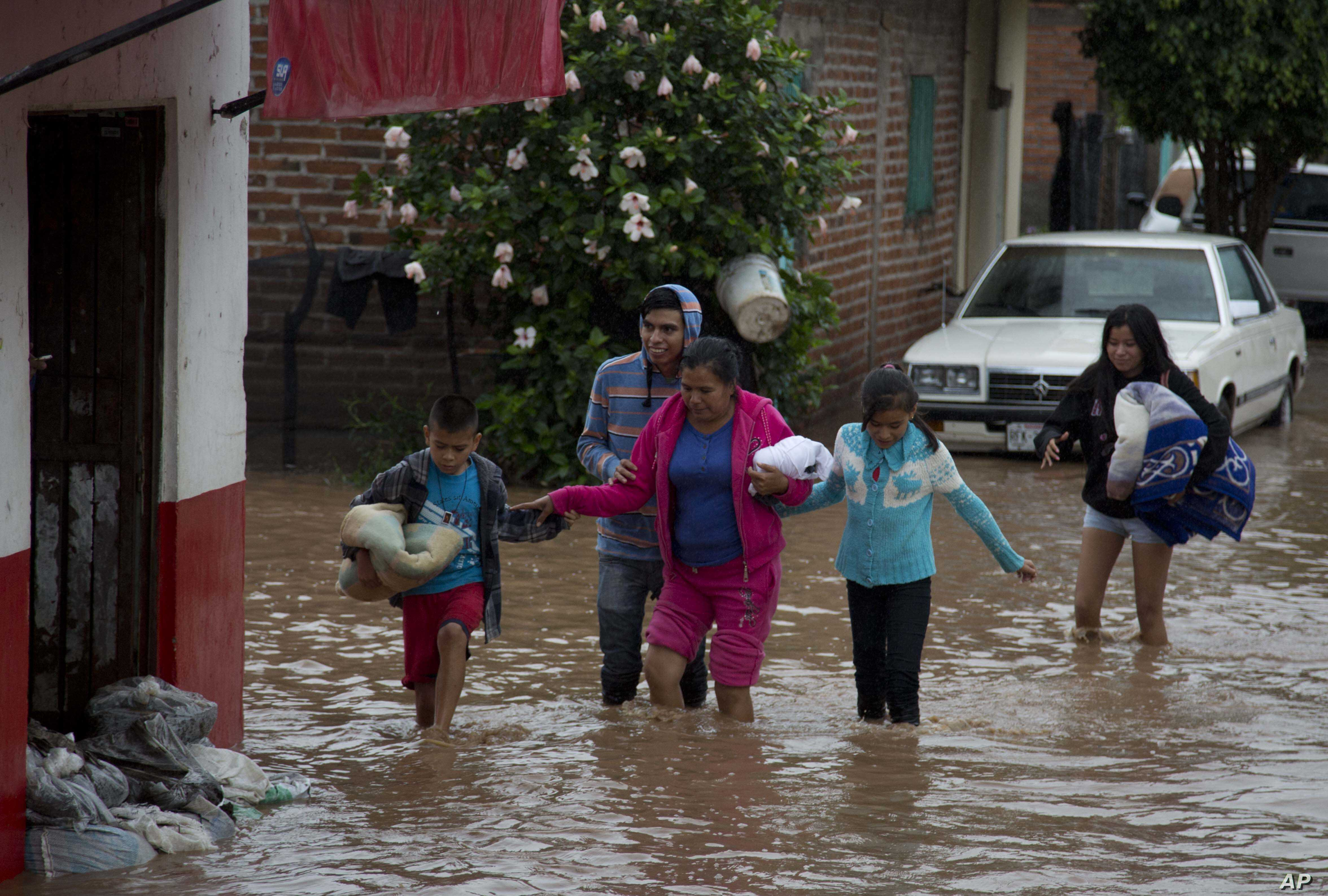 Residents walk along a flooded street in Zoatlan, Nayarit state, some 150 km northwest of Guadalajara,  Mexico, Oct. 24, 2015.
