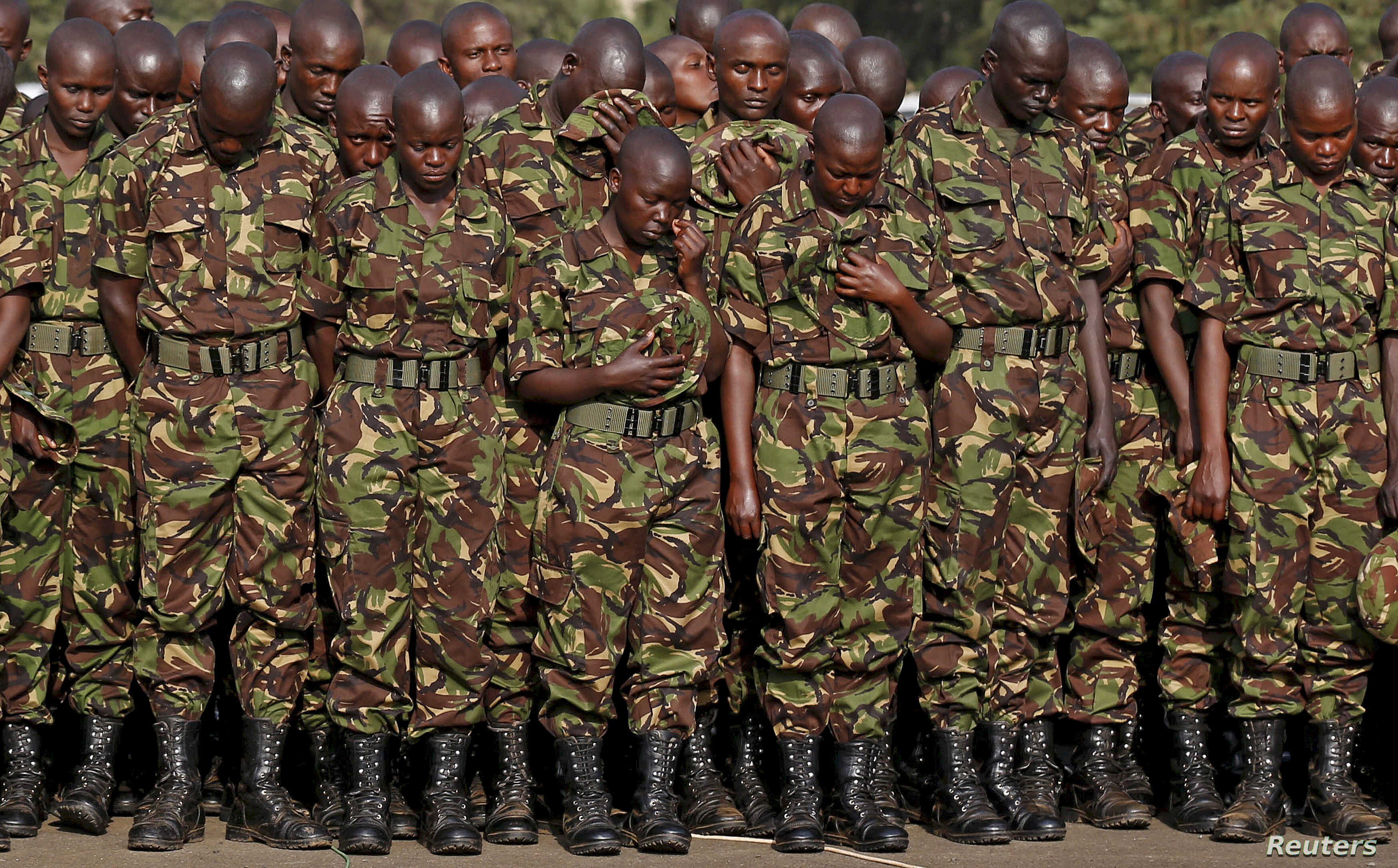 FILE - Members of the Kenya Defence Forces say prayers to pay respects to the Kenyan soldiers serving in the African Union Mission in Somalia (AMISOM), who were killed in El Adde during an attack, at a memorial mass at the Moi Barracks in Eldoret, Ja...