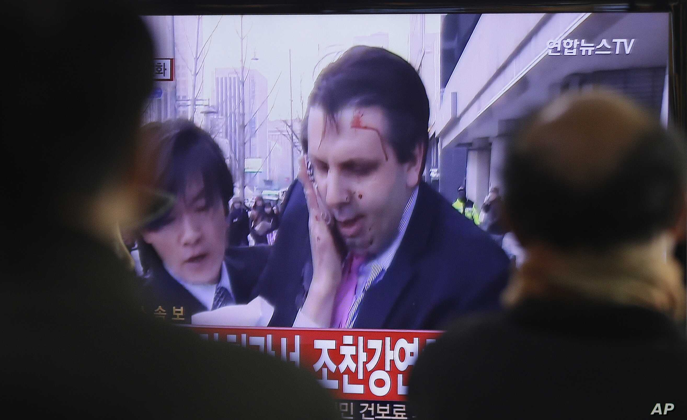 South Korean men watch a TV news program reporting U.S. Ambassador to South Korea Mark Lippert injured in a knife attack at Seoul railway station in Seoul, South Korea, Thursday, March 5, 2015. Lippert was slashed on the face and wrist by a man wield...