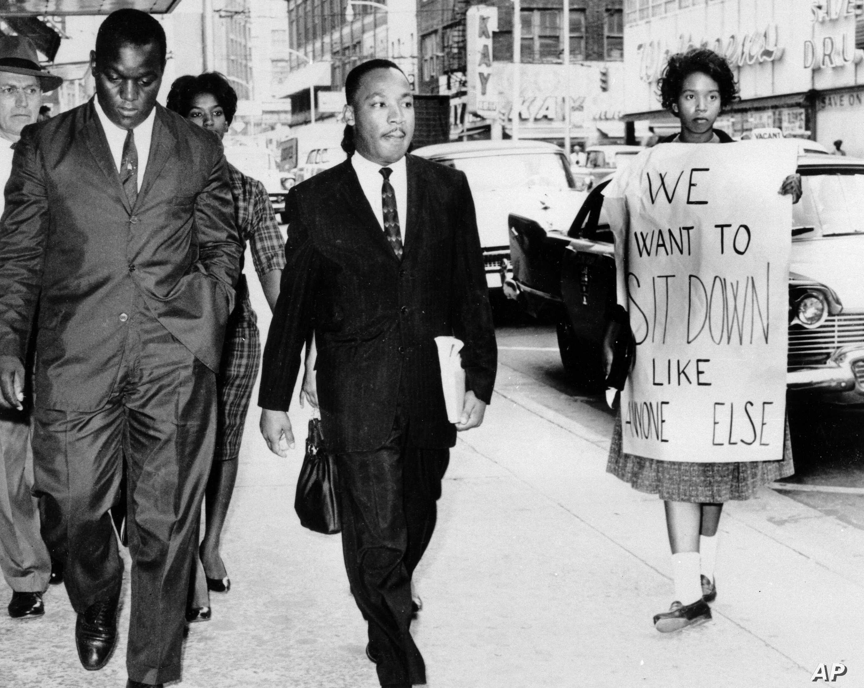 Dr. Martin Luther King Jr. under arrest by Atlanta Police Captain R.E. Little, left rear, passes through a picket line in front of a downtown department store on Oct. 9, 1960.