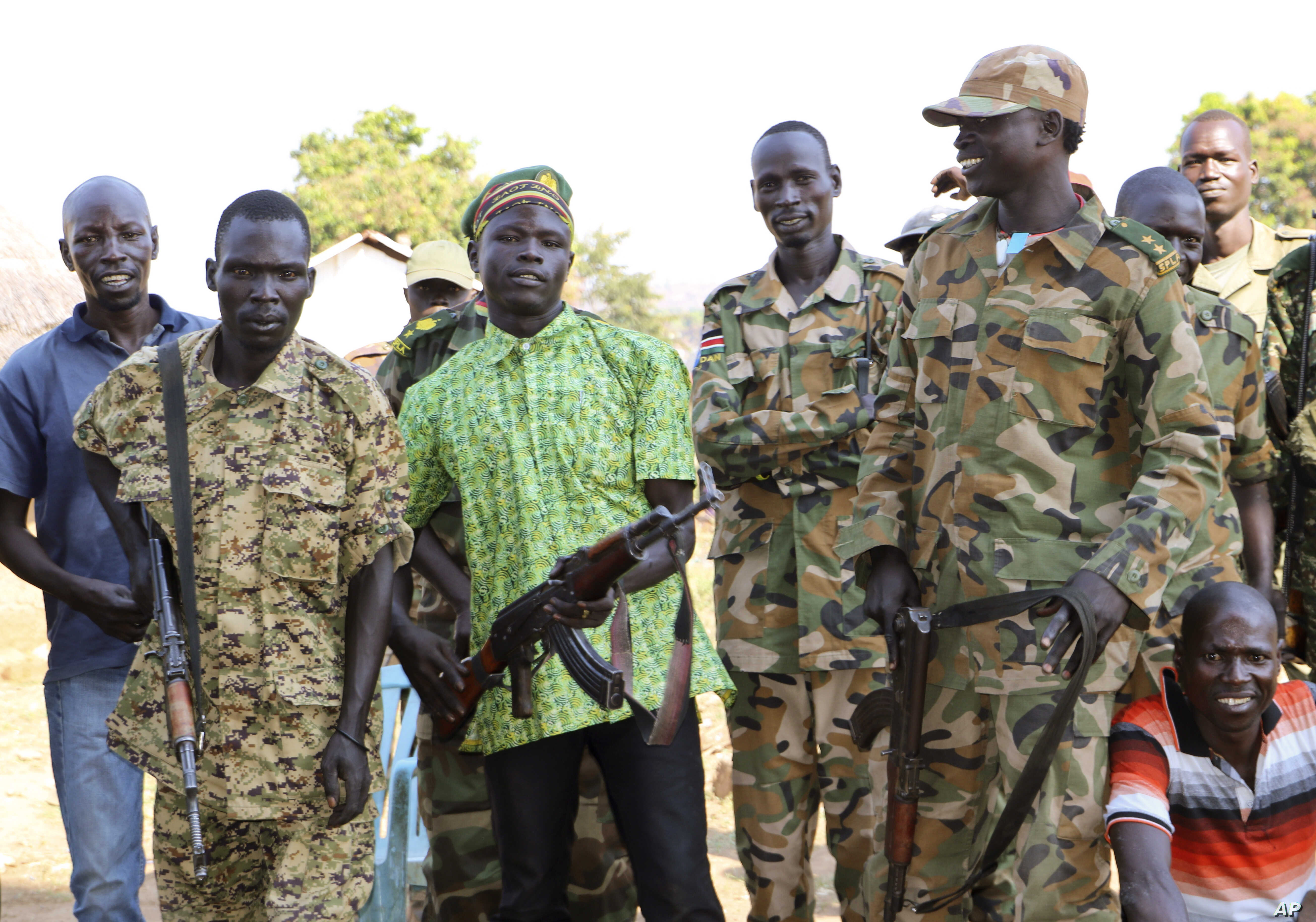 FILE - In this photo taken Jan. 6, 2019, government and opposition soldiers pose for a picture in the government barracks in Kajo Keji town, where 10 opposition soldiers were staying with the government troops in a makeshift soldier swap, in Kajo Kej...