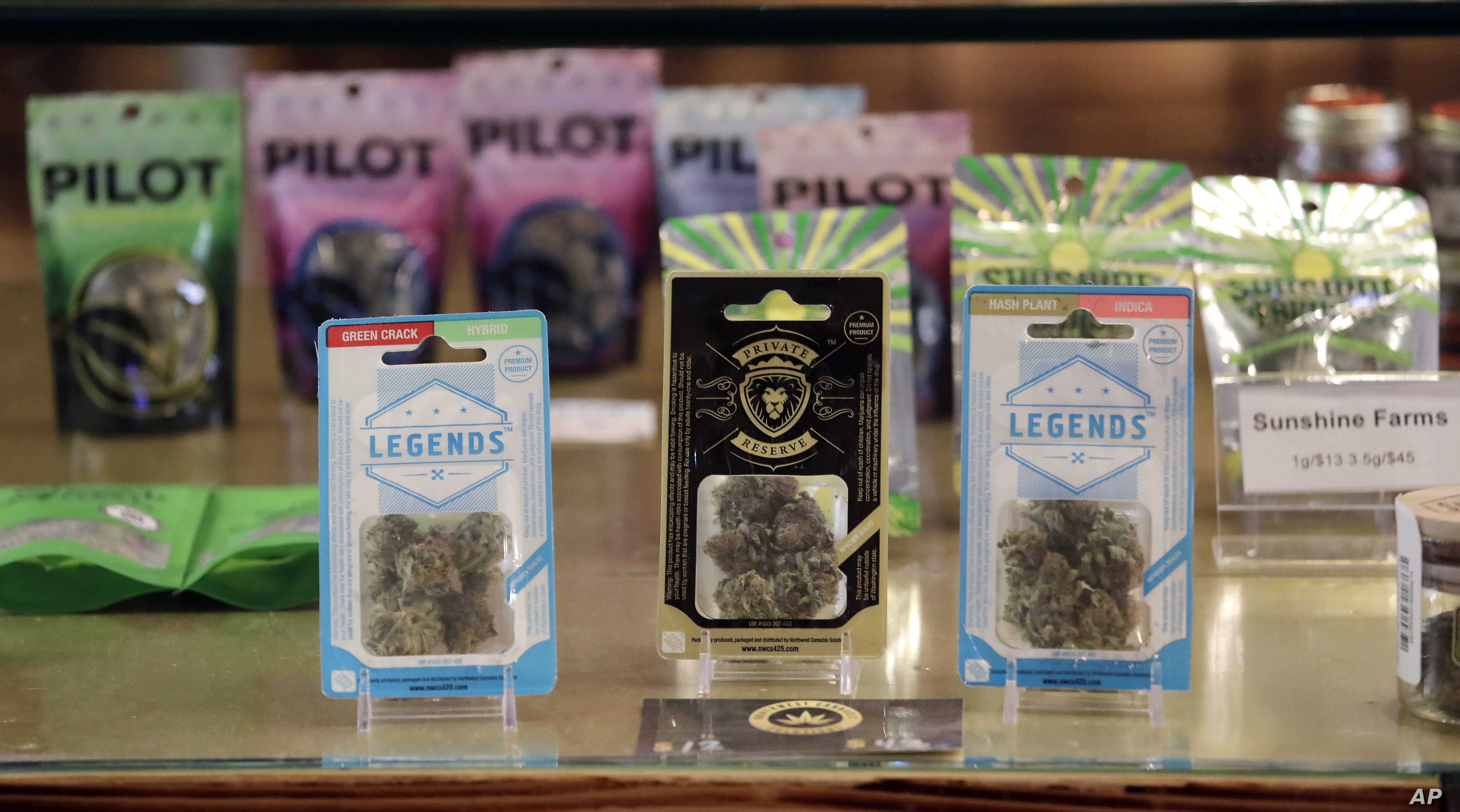 Marijuana products fill a display cabinet in the Herban Legends pot shop, Jan. 4, 2018, in Seattle.