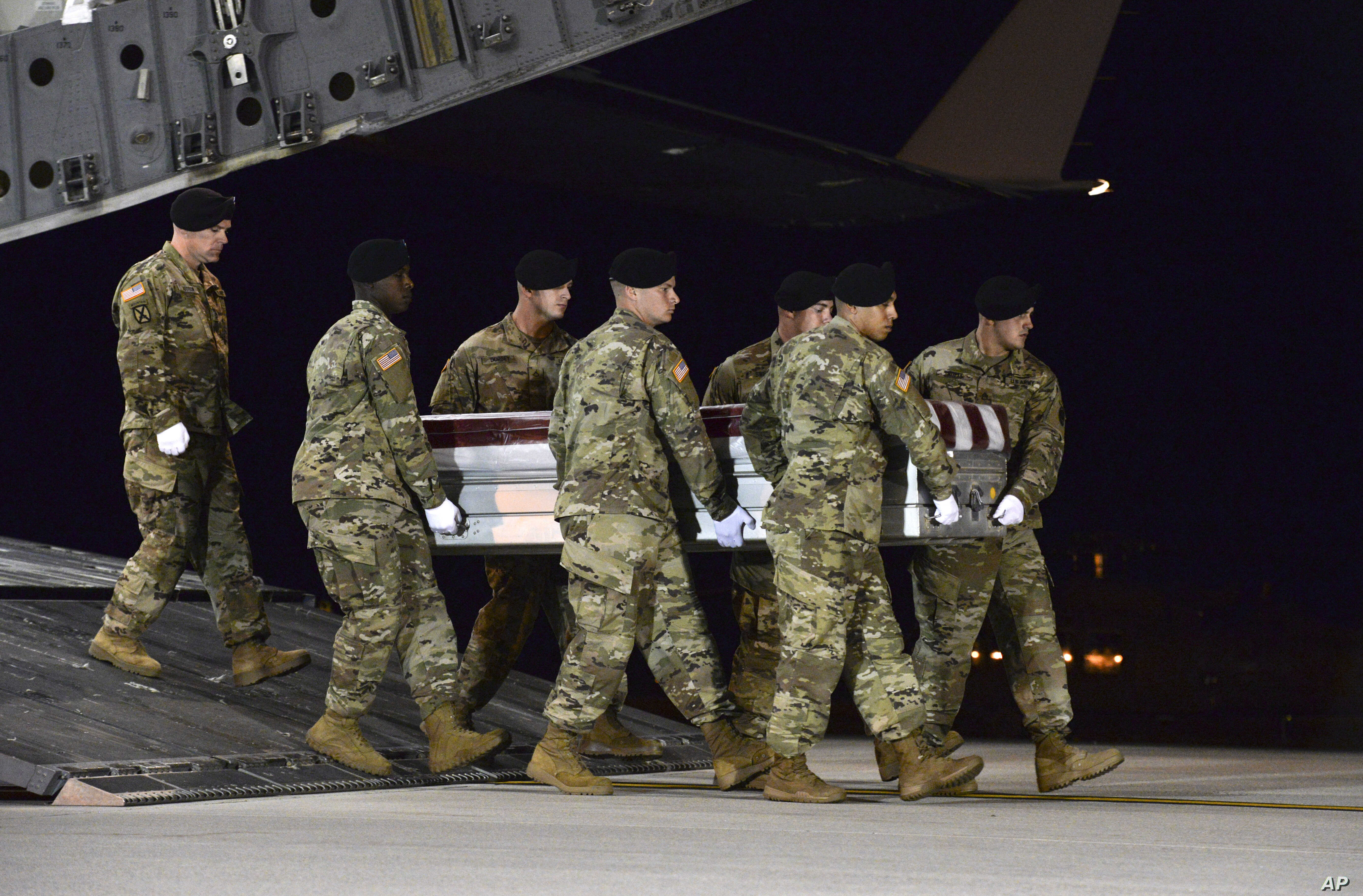 FILE - In this Oct. 5, 2017 file photo, a U.S. Army carry team transfers the remains of Army Staff Sgt. Dustin Wright  upon arrival at Dover Air Force Base, Delaware. Wright was one of four U.S. troops killed in an ambush by dozens of Islamic extremi...