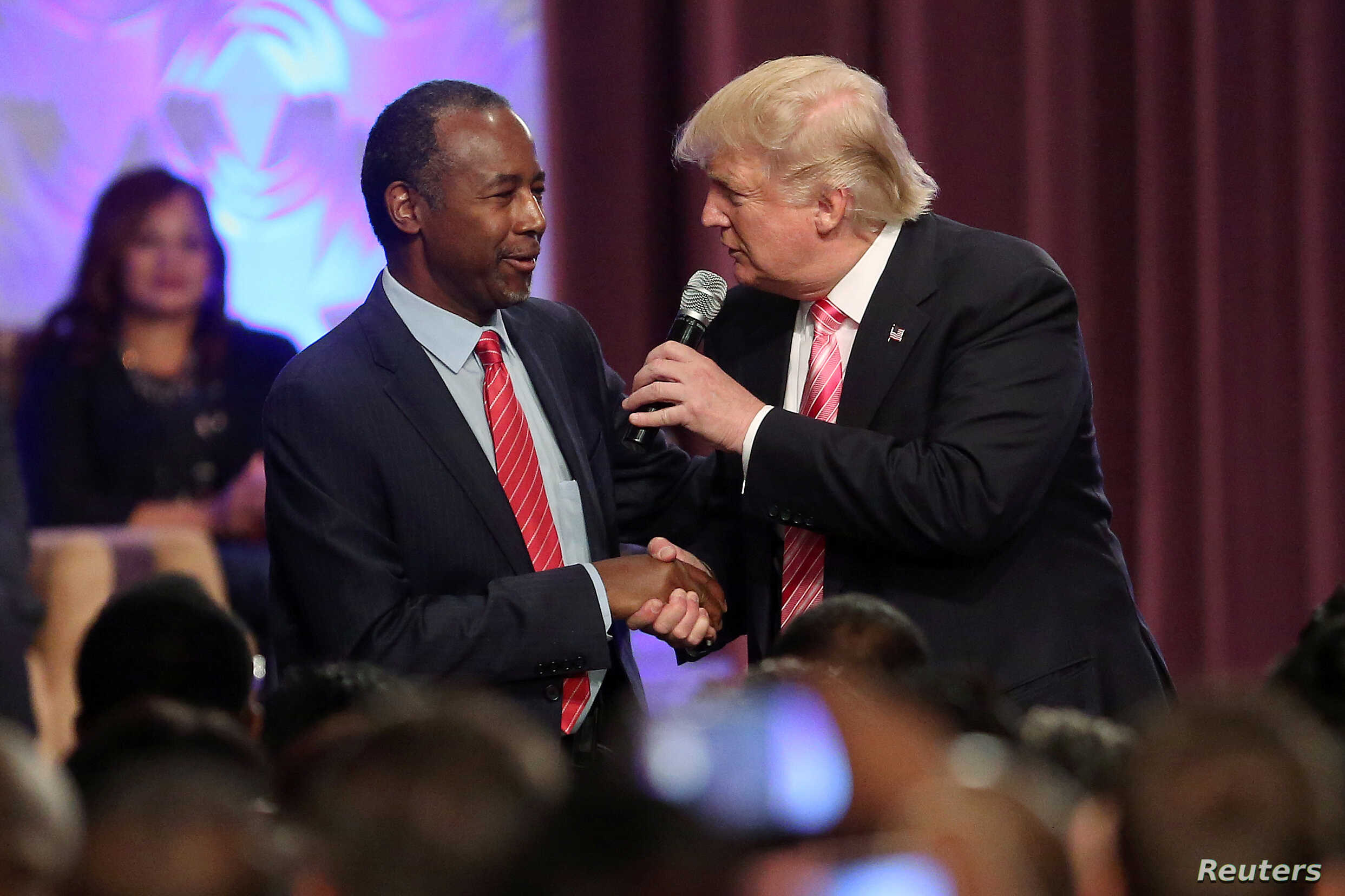 File - Donald Trump shakes hands with Ben Carson as he attends a church service in Detroit, Michigan, U.S., Sept. 3, 2016.