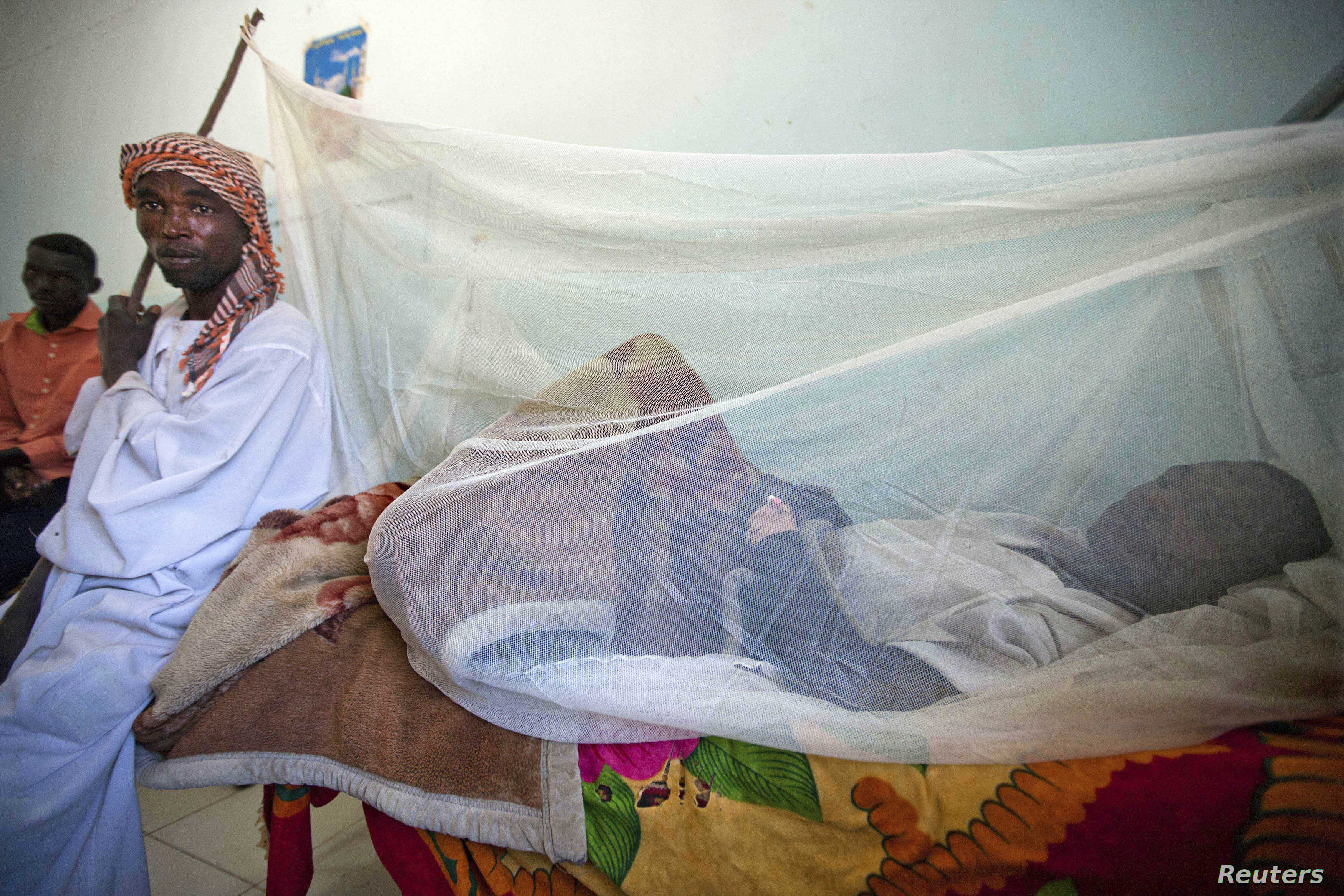 FILE - Adam Abdalah (L), a farmer from West Darfur's Adar, accompanies his son Yassim Adam who is being treated for yellow fever at the Teaching Hospital in El Geneina in this Nov. 14, 2012 handout.