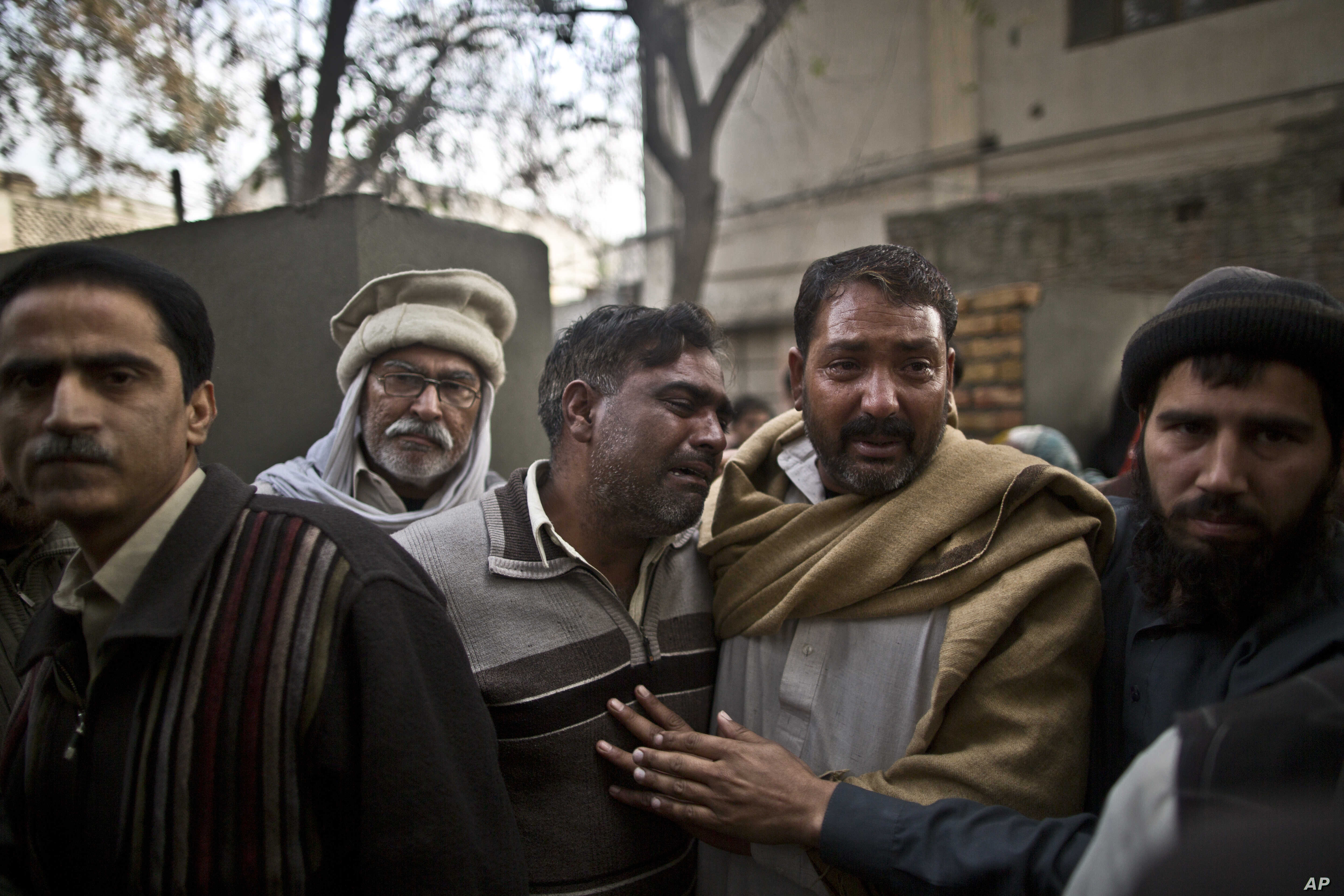 Uncles of a student who was killed in a suicide bombing comfort each other as his body is loaded to an ambulance for burial, at a hospital in Rawalpindi, Pakistan, Jan. 20, 2014.