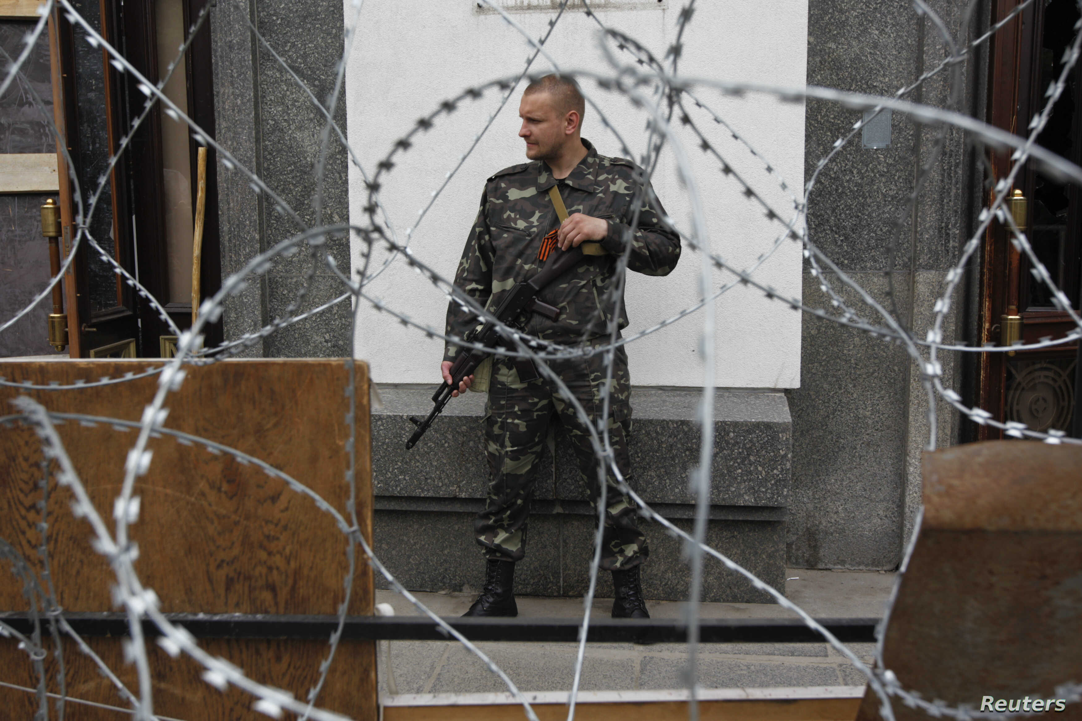 A pro-Russian gunman stands guard outside an administrative building in the eastern Ukrainian city of Luhansk May 12, 2014.