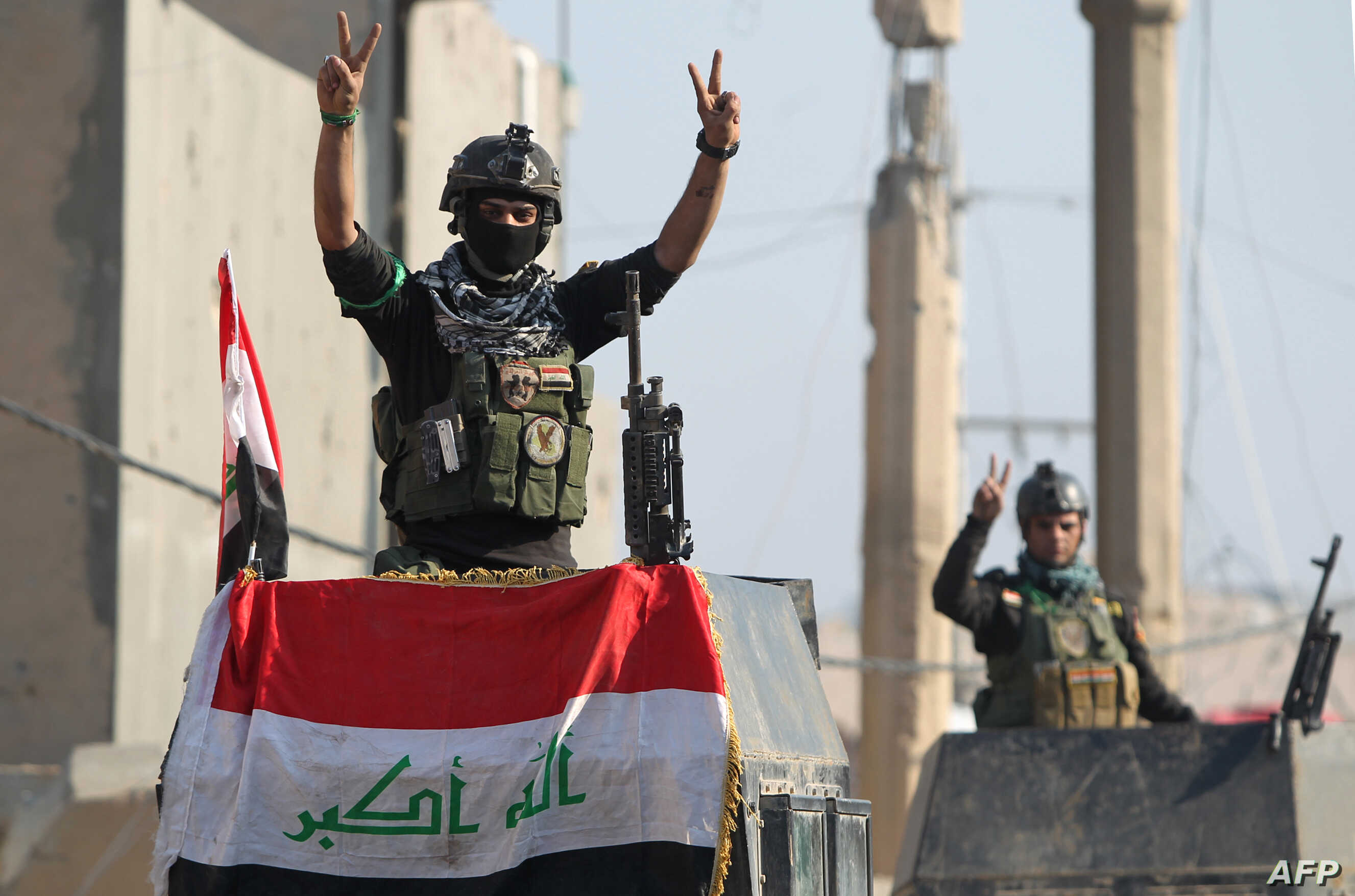 """Members of Iraq's elite counter-terrorism service flash the """"V"""" for victory sign, Dec. 29, 2015 in the city of Ramadi, the capital of Iraq's Anbar province, about 110 kilometers west of Baghdad, after Iraqi forces recaptured it from the Islamic State..."""