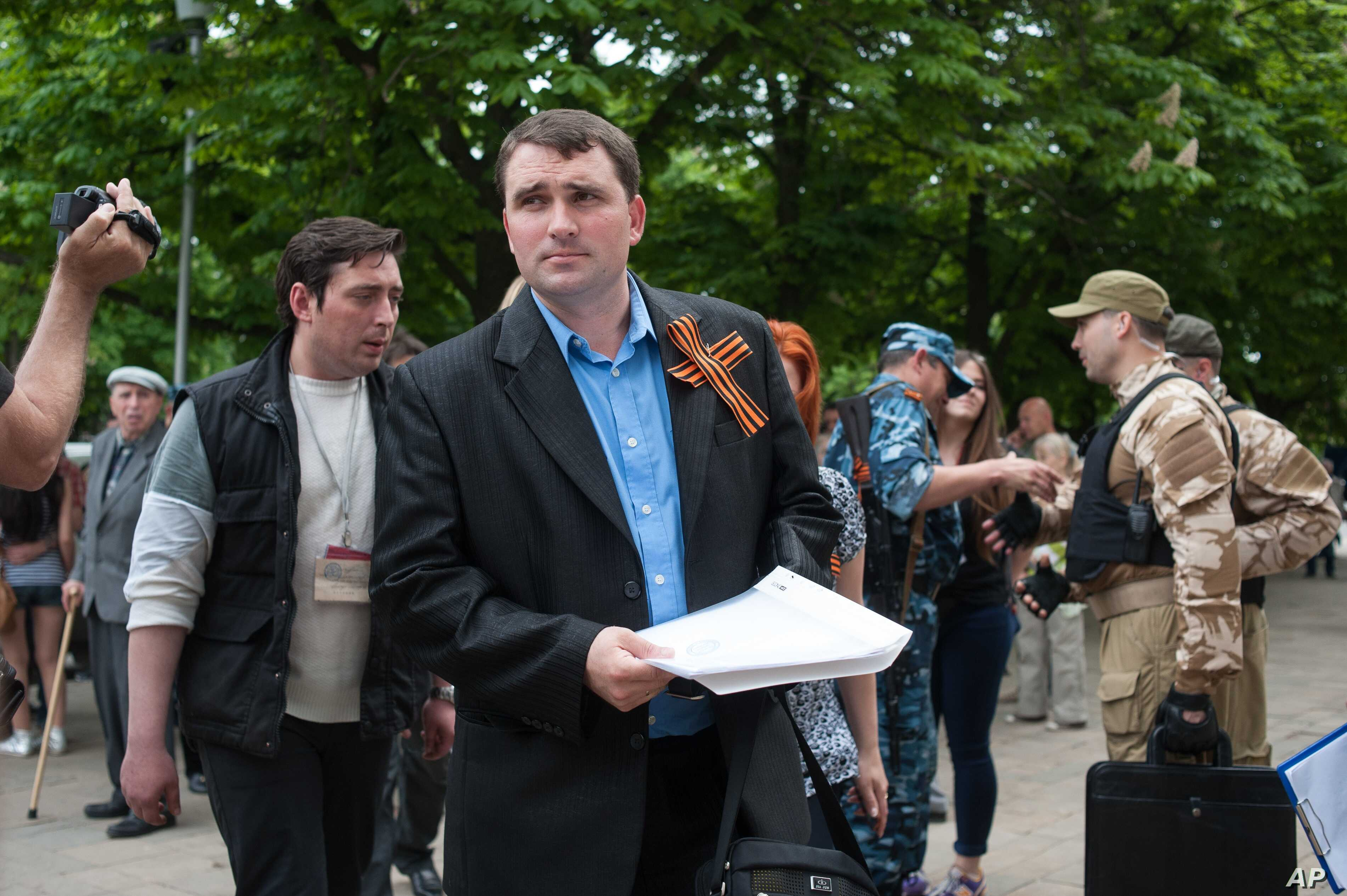 Secessionist referendum official Alexander Malyhin holds a document as he speaks to journalists in the eastern Ukrainian city of Luhansk May 12, 2014.