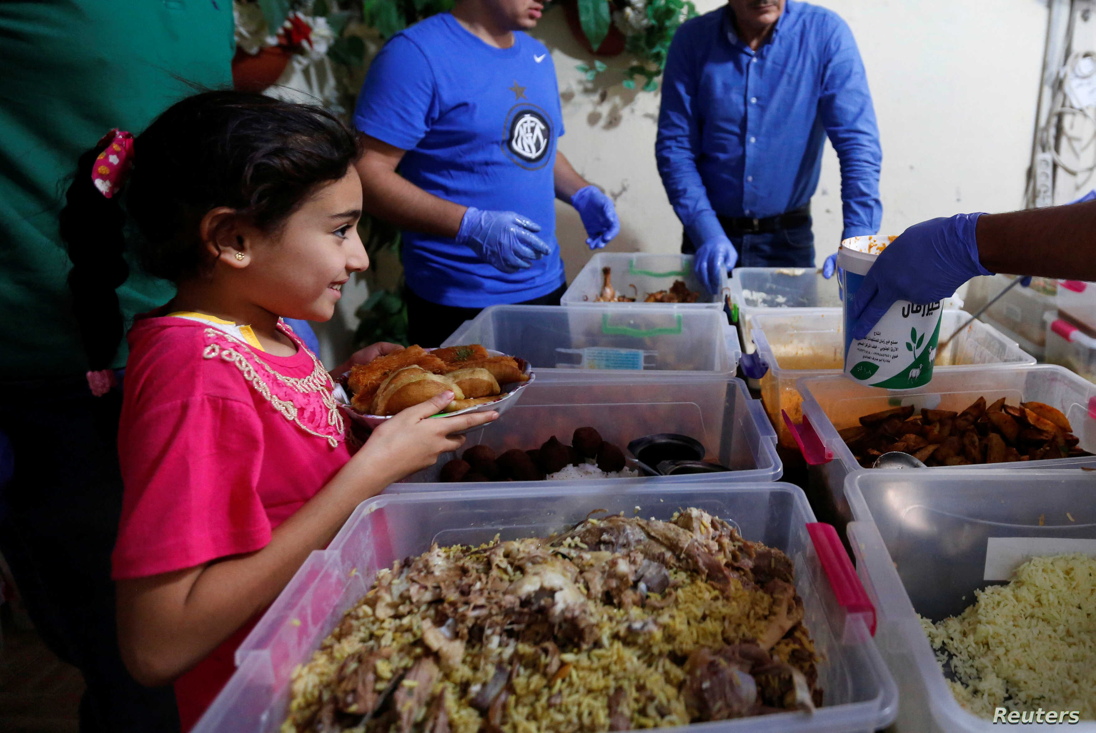A girl receives a meal provided through the initiative, Family Kitchen, in Al-Baqaa Palestinian refugee camp, near Amman, Jordan, June 11, 2018.