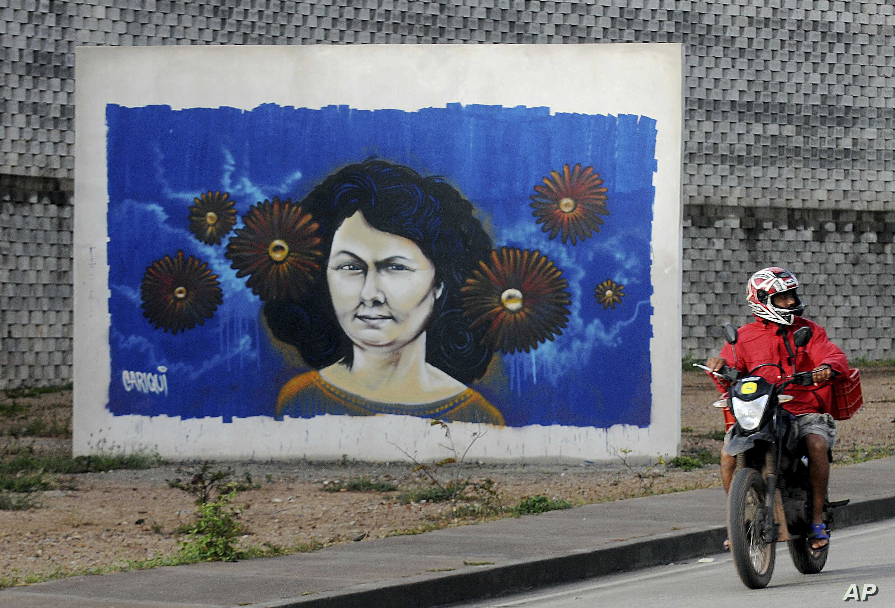 FILE - A motorcyclist rides past a mural of slain environmentalist and indigenous leader Berta Caceres in Tegucigalpa, Honduras.