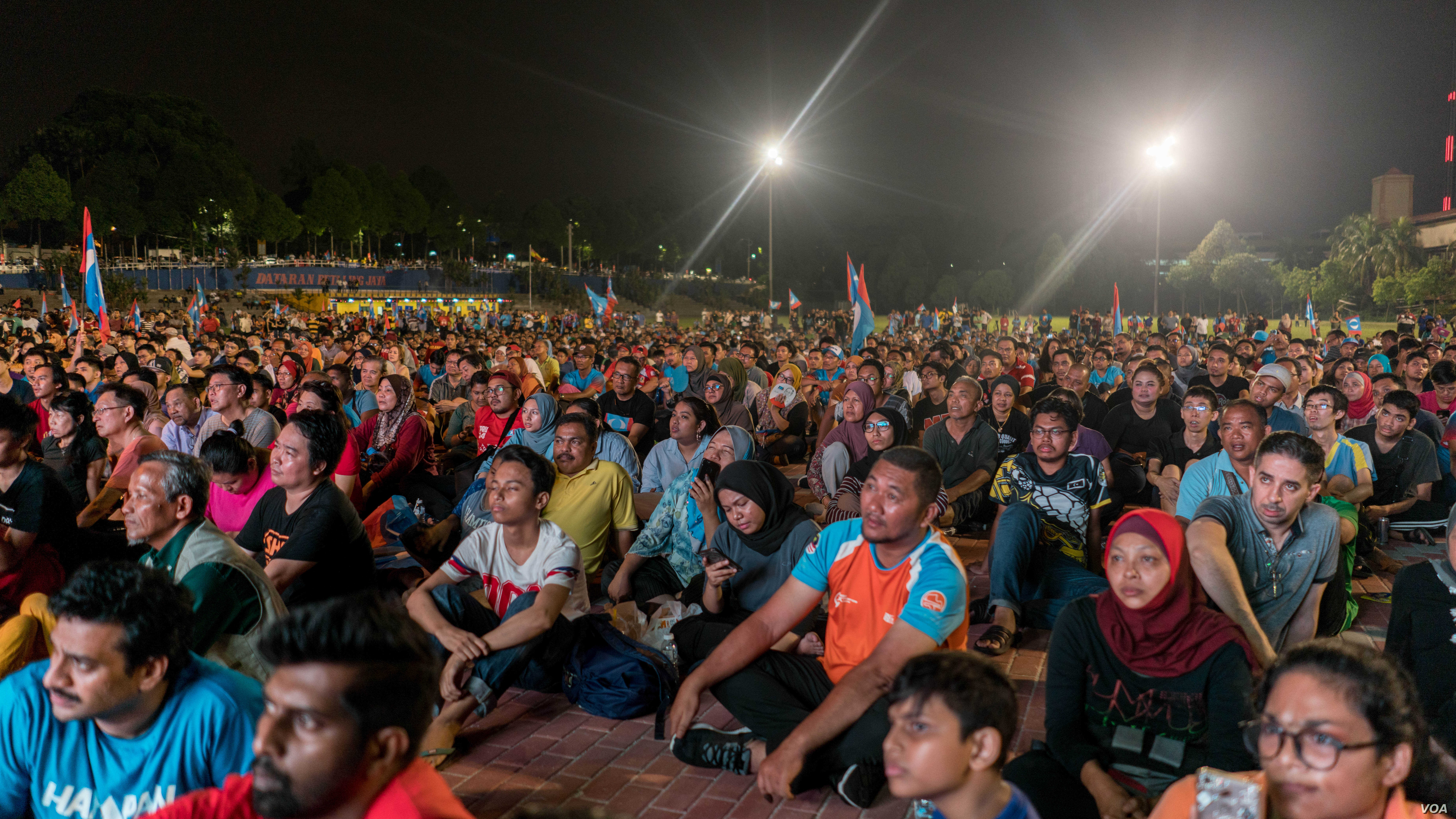 A crowd of opposition supporters wait as results are announced from the Malaysian election, May 9, 2018.