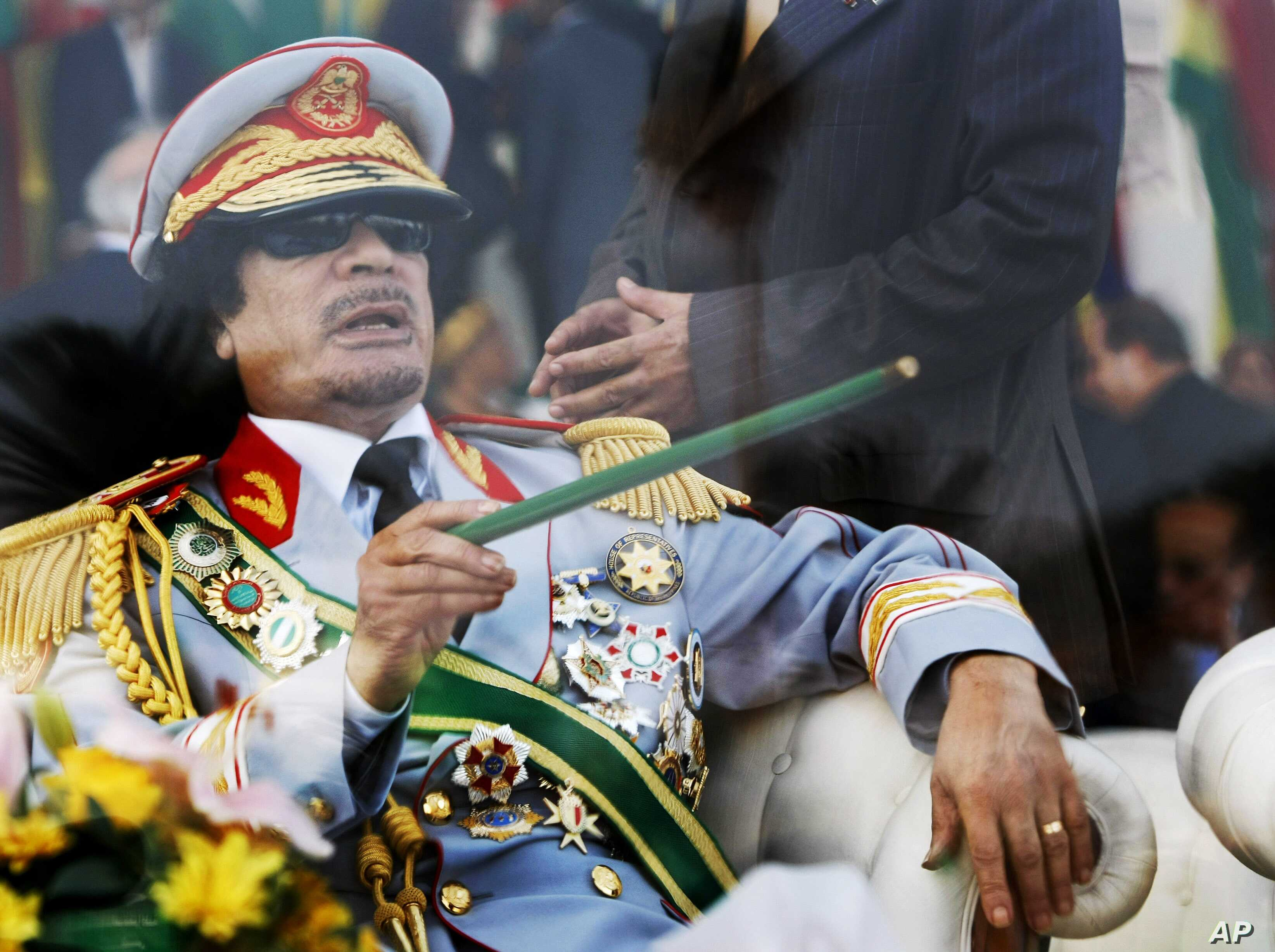 FILE - In this Tuesday, Sept. 1, 2009 file photo, Libyan leader Moammar Gadhafi gestures with a green cane as he takes his seat behind bulletproof glass for a military parade in Green Square, Tripoli, Libya.