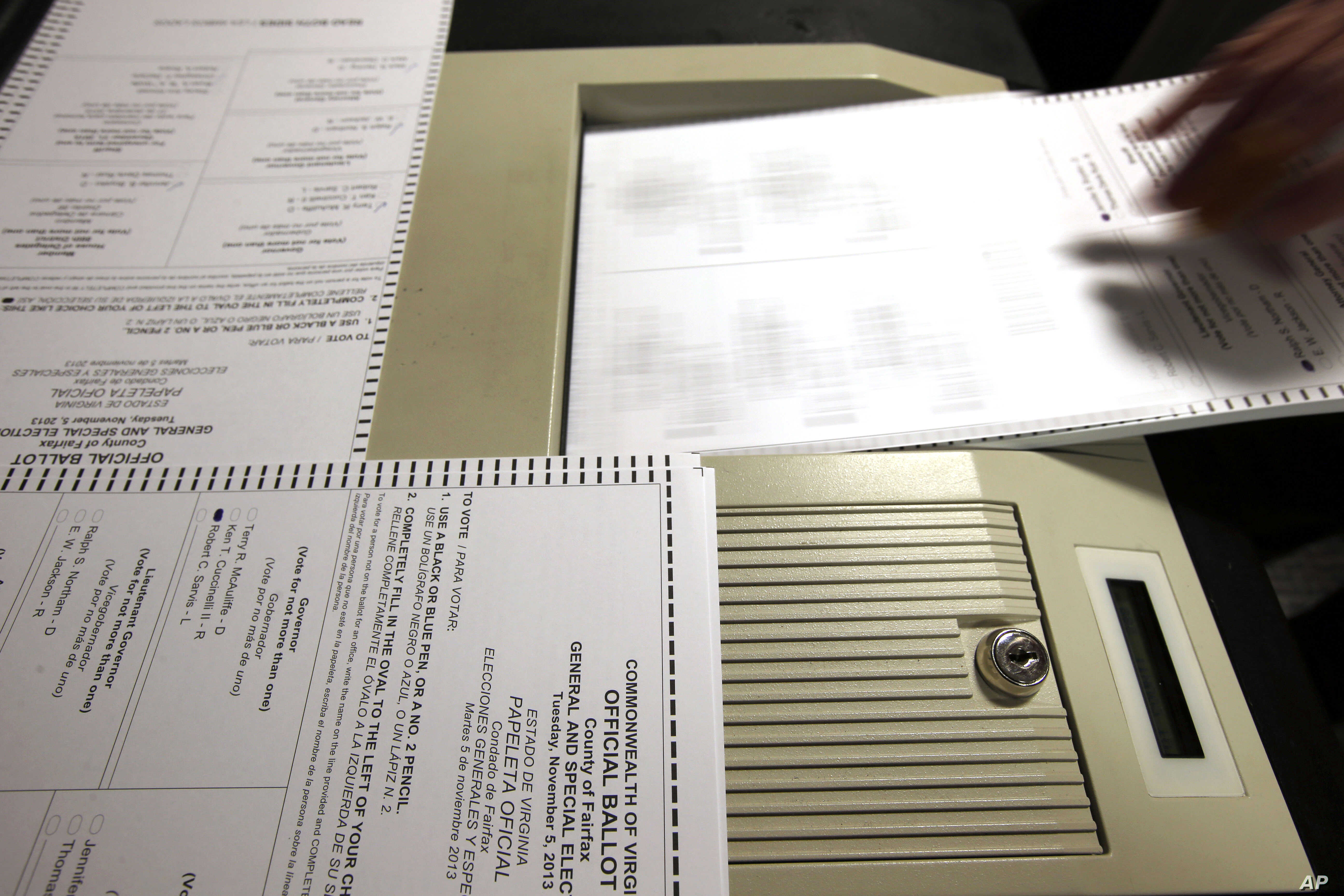 FILE - Paper ballots are fed into a machine during a recount in the 2013 attorney general election in Virginia.