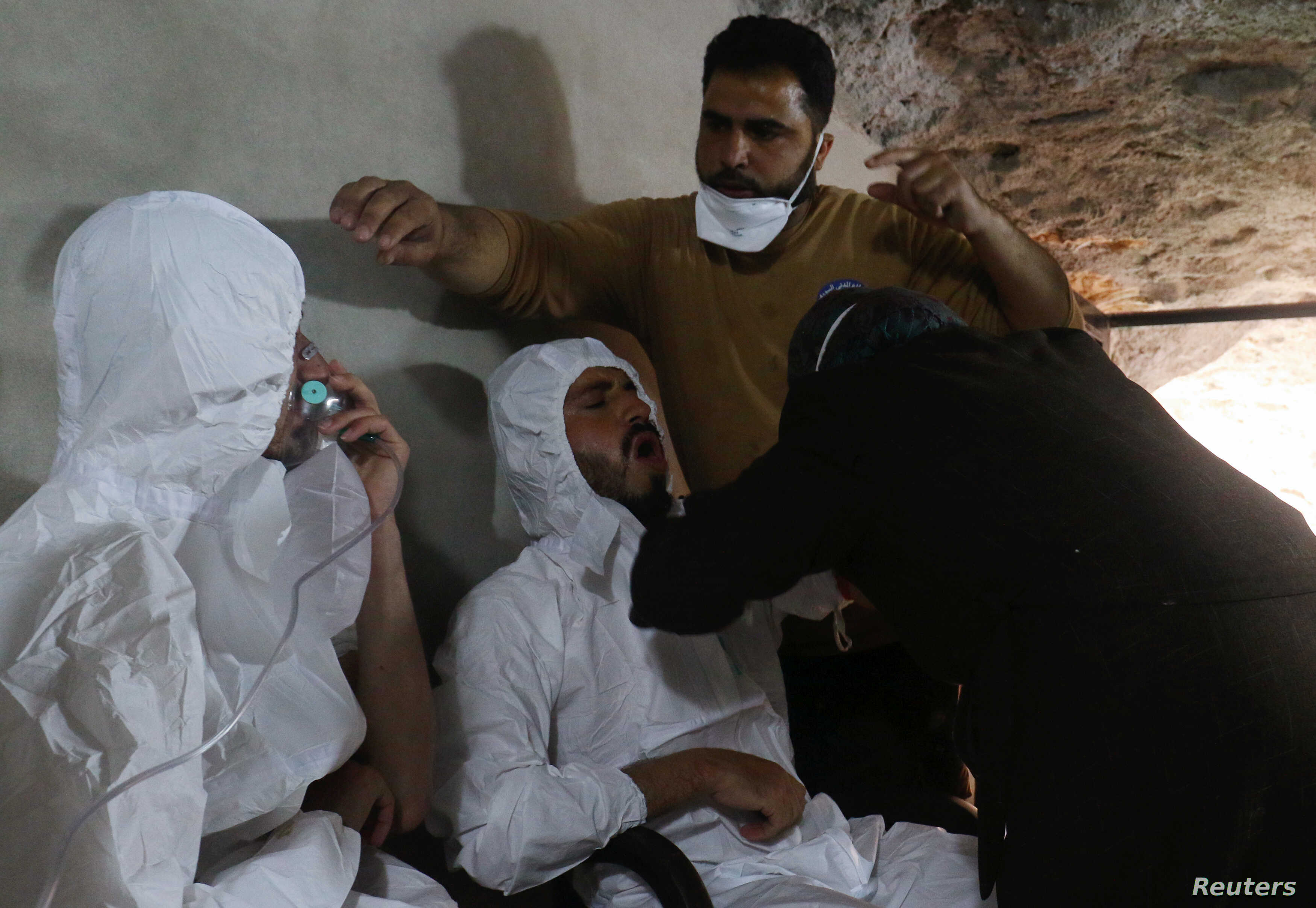 A man breathes through an oxygen mask as another one receives treatments, after what rescue workers described as a suspected gas attack in the town of Khan Sheikhoun in rebel-held Idlib, Syria, April 4, 2017.