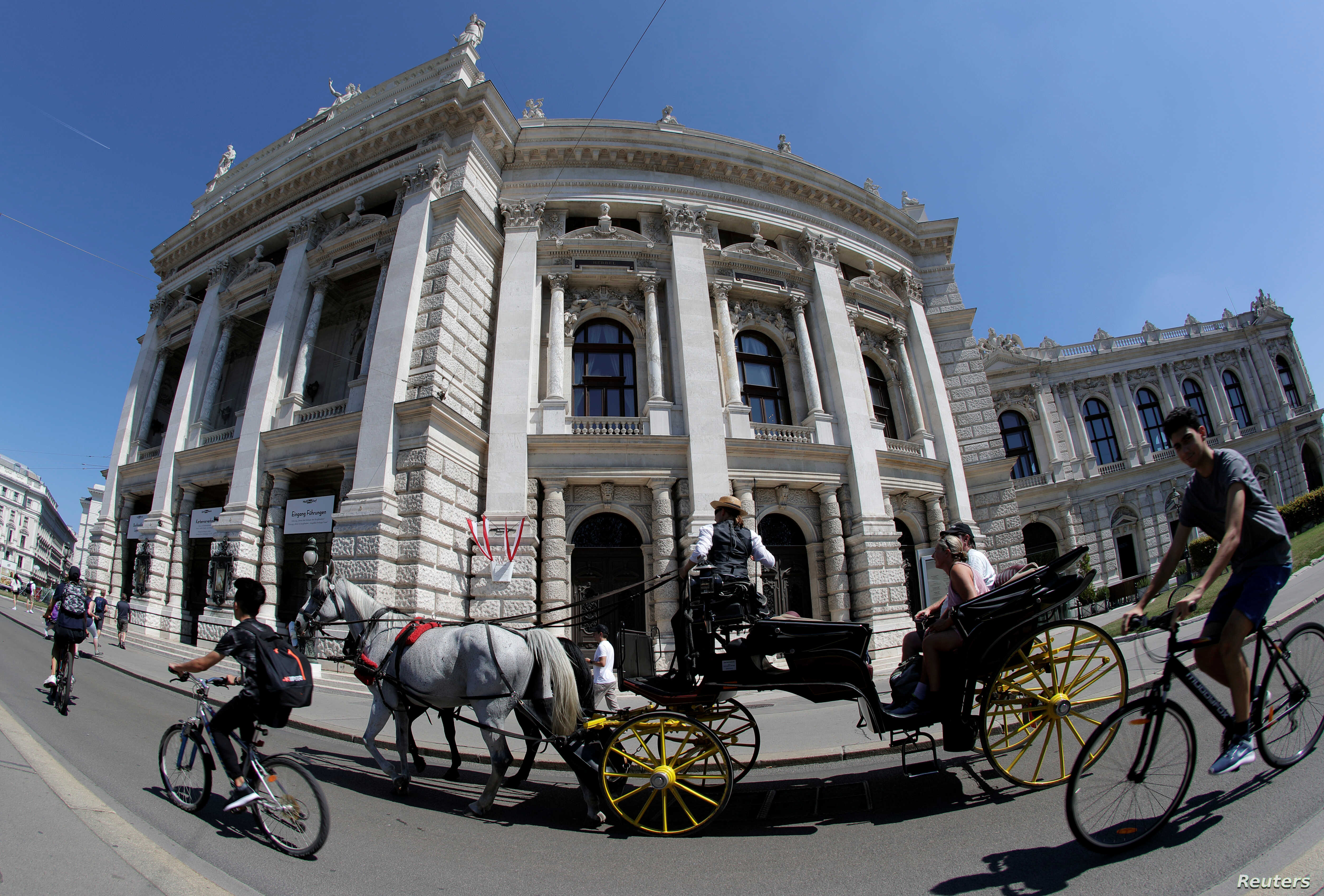 A traditional Fiaker horse carriage passes Burgtheater theatre in Vienna, Austria, Aug. 13, 2018.