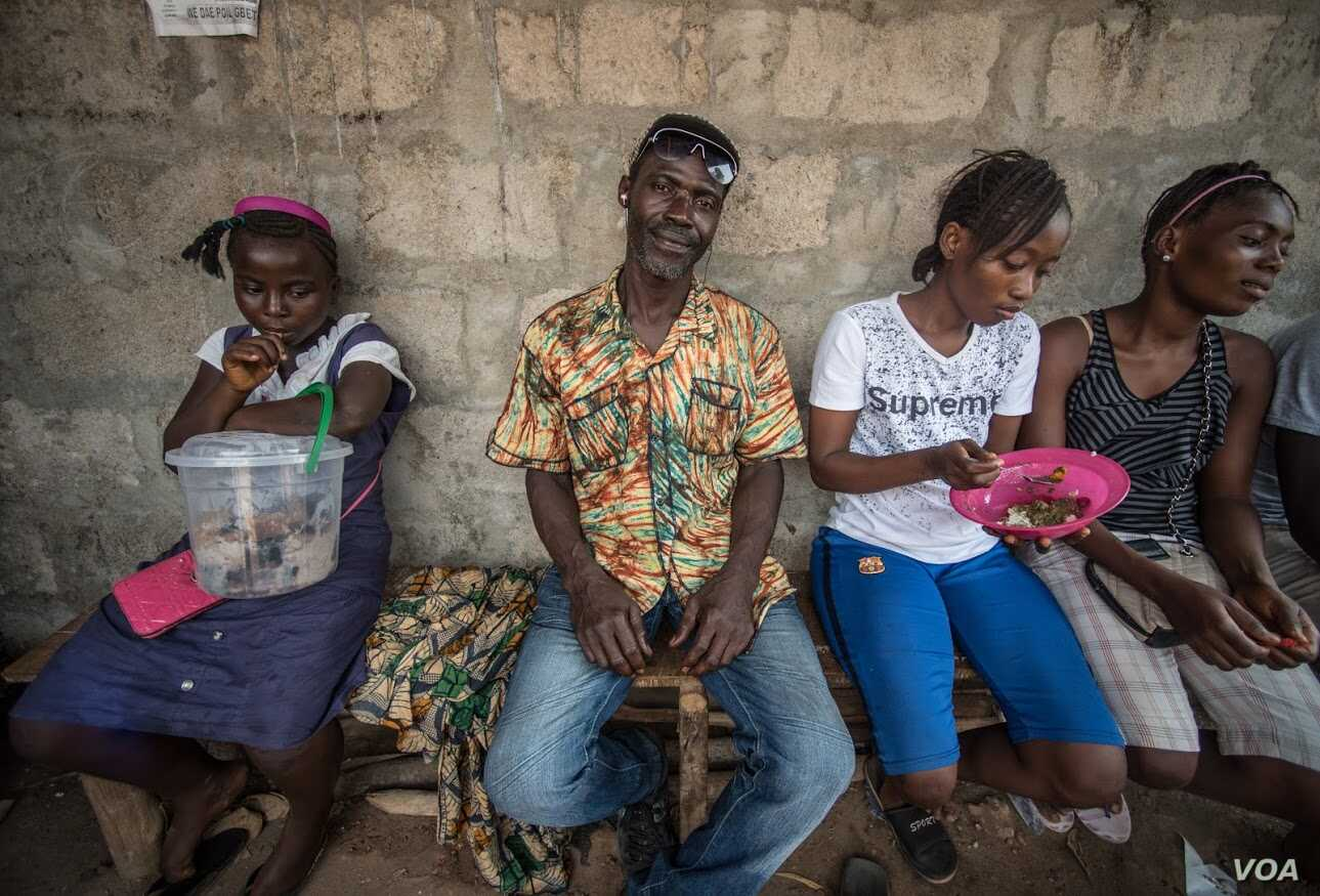 Mohammed Sankoh sits at a roadside food stall, Sierra Leone. (O. Acland for VOA)