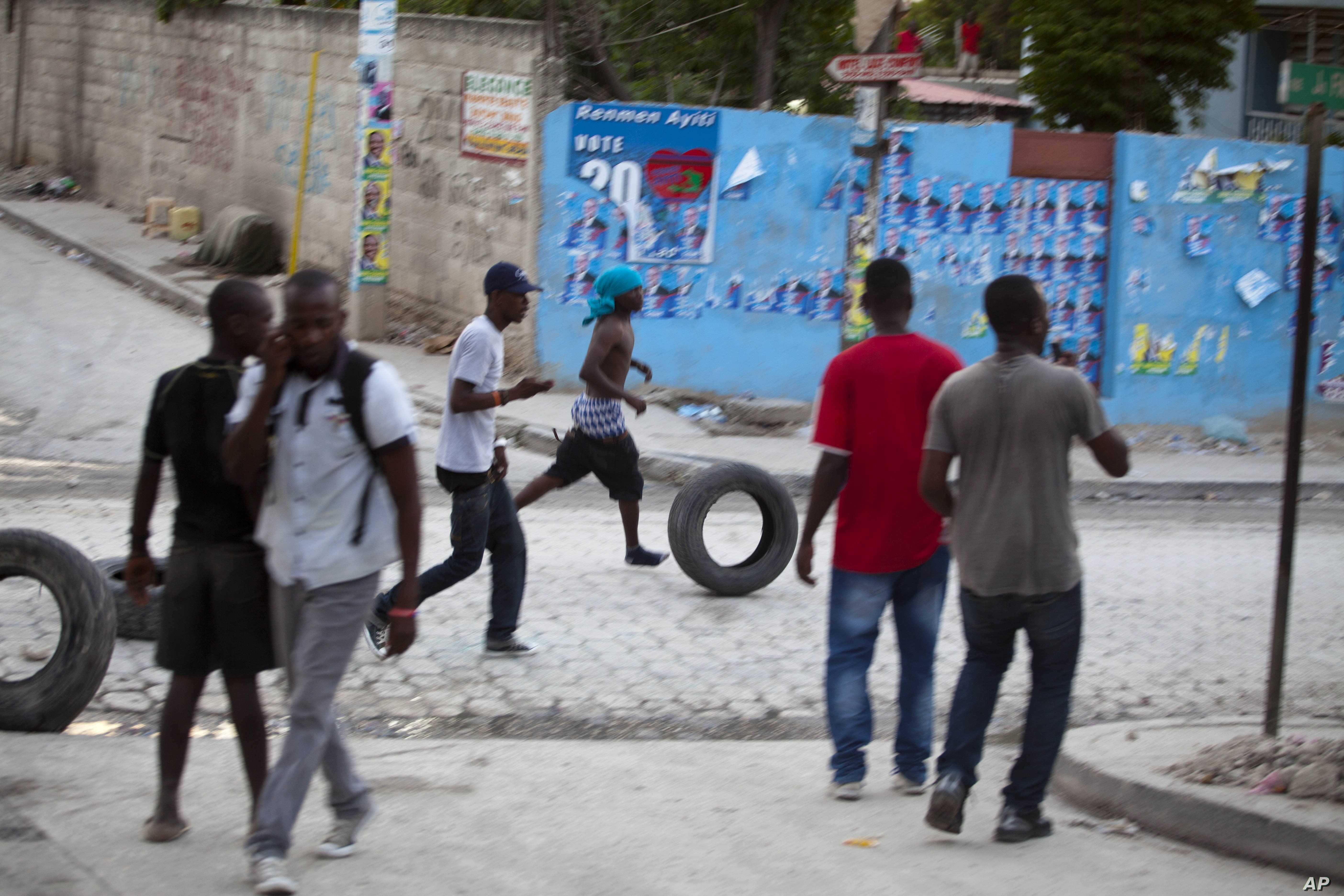 Supporters of Presidential candidate Moise Jean-Charles move tires before burning them during protests against official results just announced by the Electoral Council in the neighborhood of Delmas 33, Port-au-Prince, Haiti, Thursday Nov. 5, 2015.