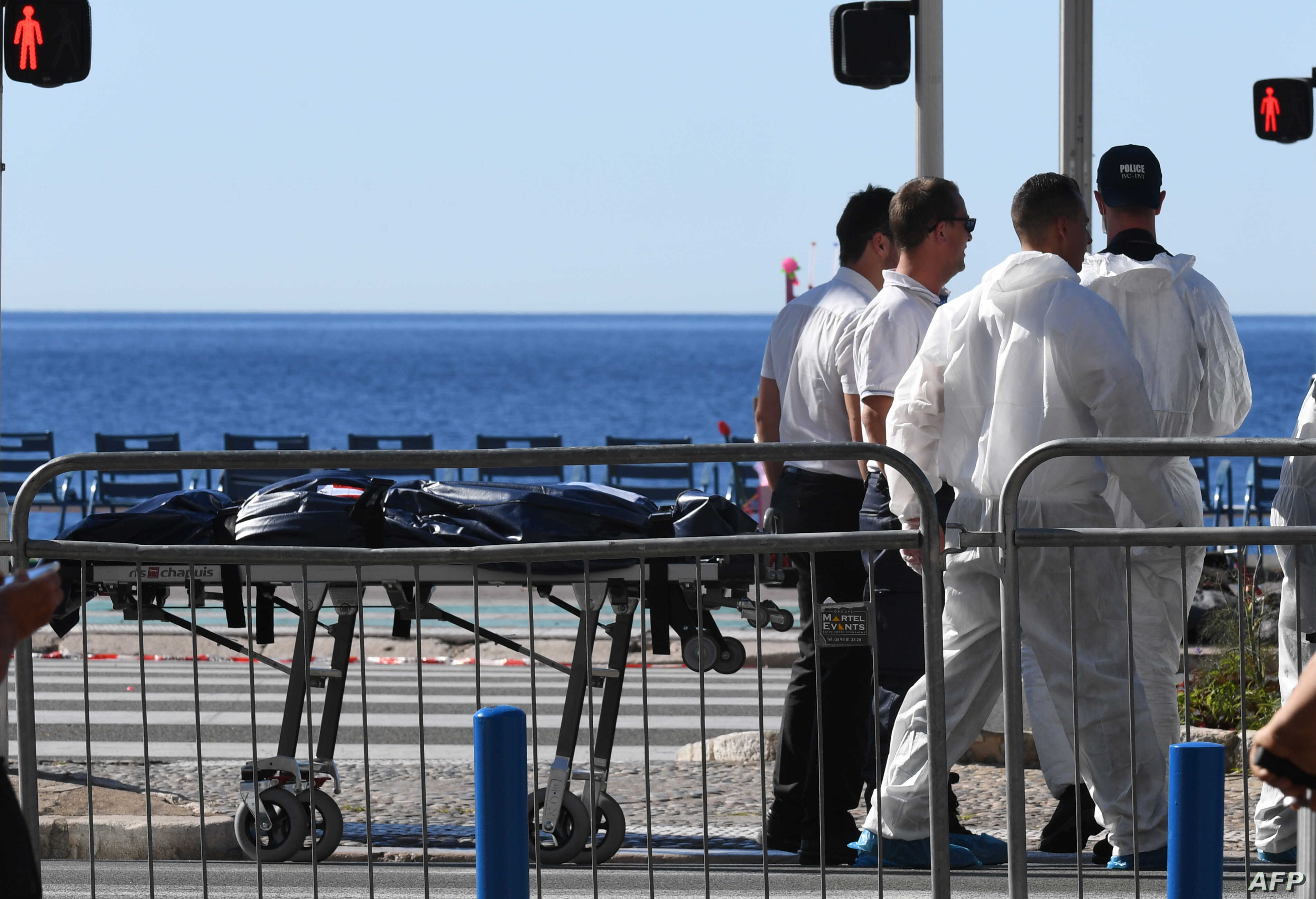 Forensics experts evacuate a dead body on the Promenade des Anglais seafront in the French Riviera town of Nice on July 15, 2016, after a gunman smashed a truck into a crowd of revelers celebrating Bastille Day.