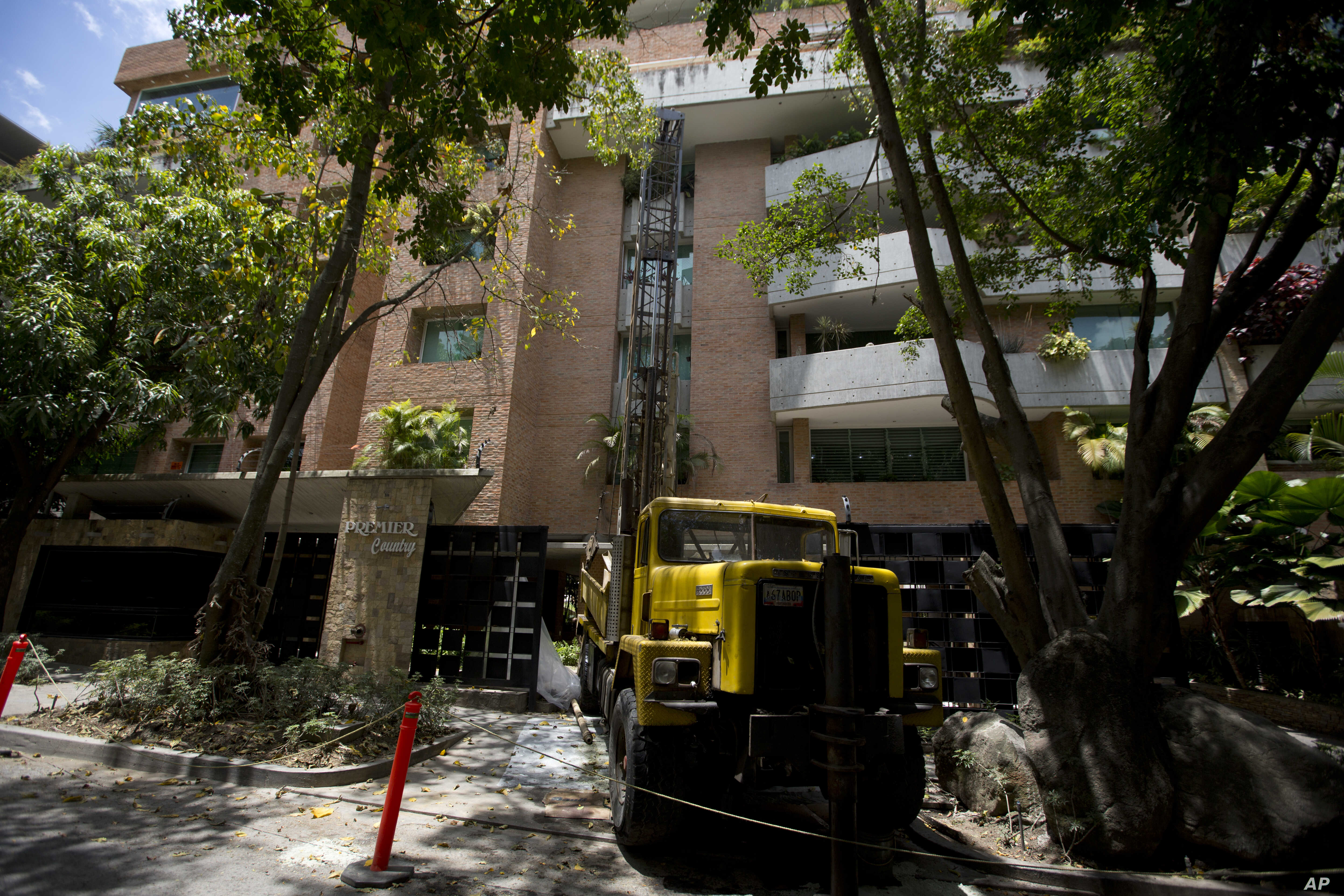 A drill creates a well during water shortages outside the luxury apartment complex in the Campo Alegre neighborhood of Caracas, Venezuela, May 31, 2018.