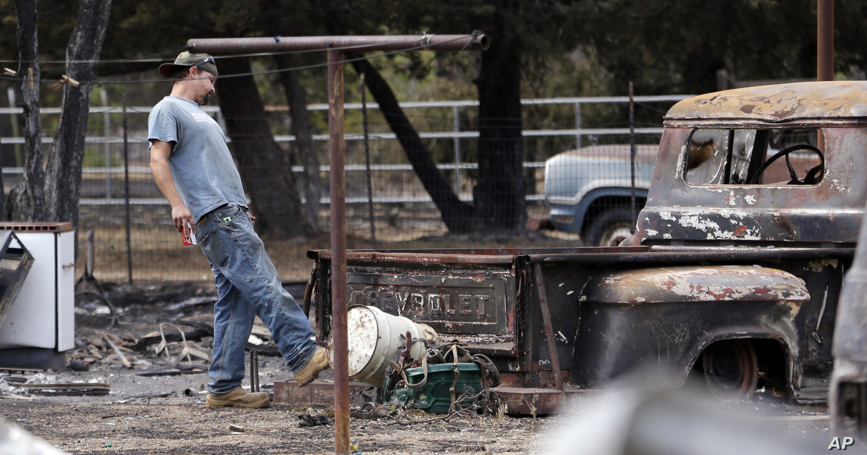 Gary Herrin angrily kicks at an old Chevrolet pickup truck destroyed in a wildfire several days earlier as he visits the family home for the first time since it burned down, Sept. 15, 2015, in Middletown, Calif.