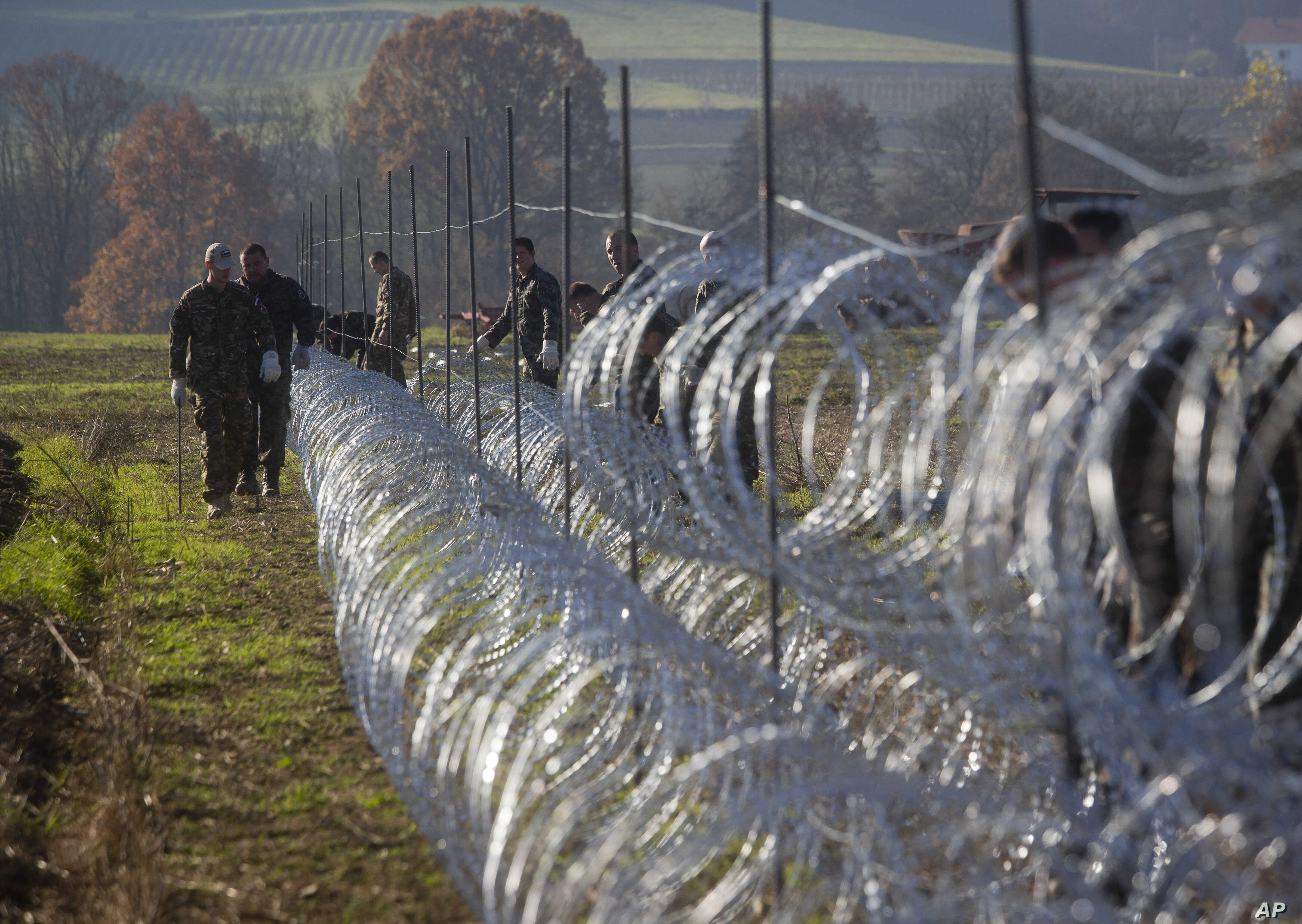 Slovenian soldiers erect a razor-wired fence on the Croatian border in Gibina, Slovenia, Nov. 11, 2015. The government aims to prevent the uncontrolled entry of more migrants in the already-overwhelmed alpine state.