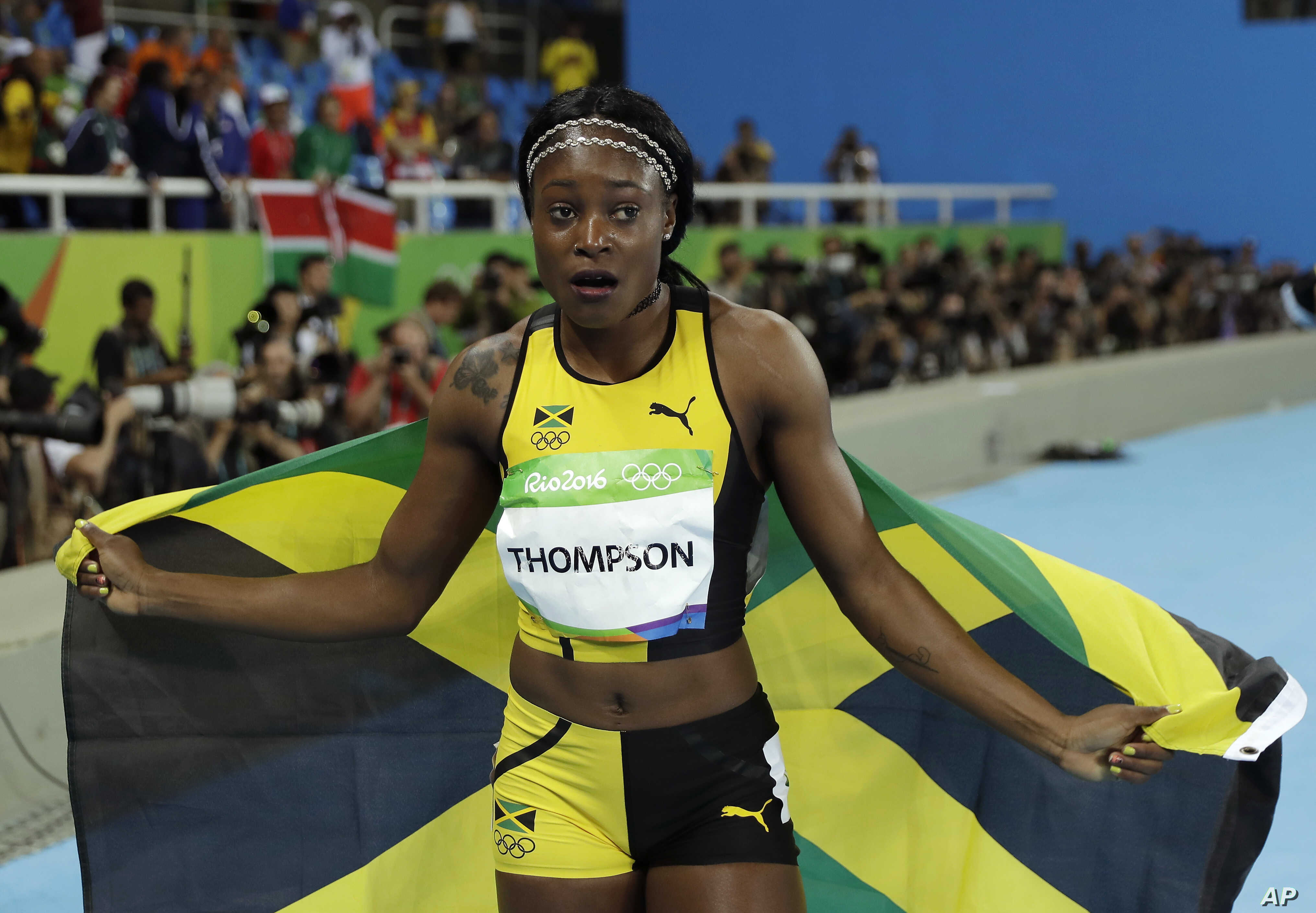 Rio Olympics Athletics: Jamaica's Elaine Thompson celebrates with the Jamaican flag after winning gold in the women's 100-meter final during the athletics competitions in the Olympic stadium of the 2016 Summer Olympics in Rio de Janeiro, Brazil, Satu...