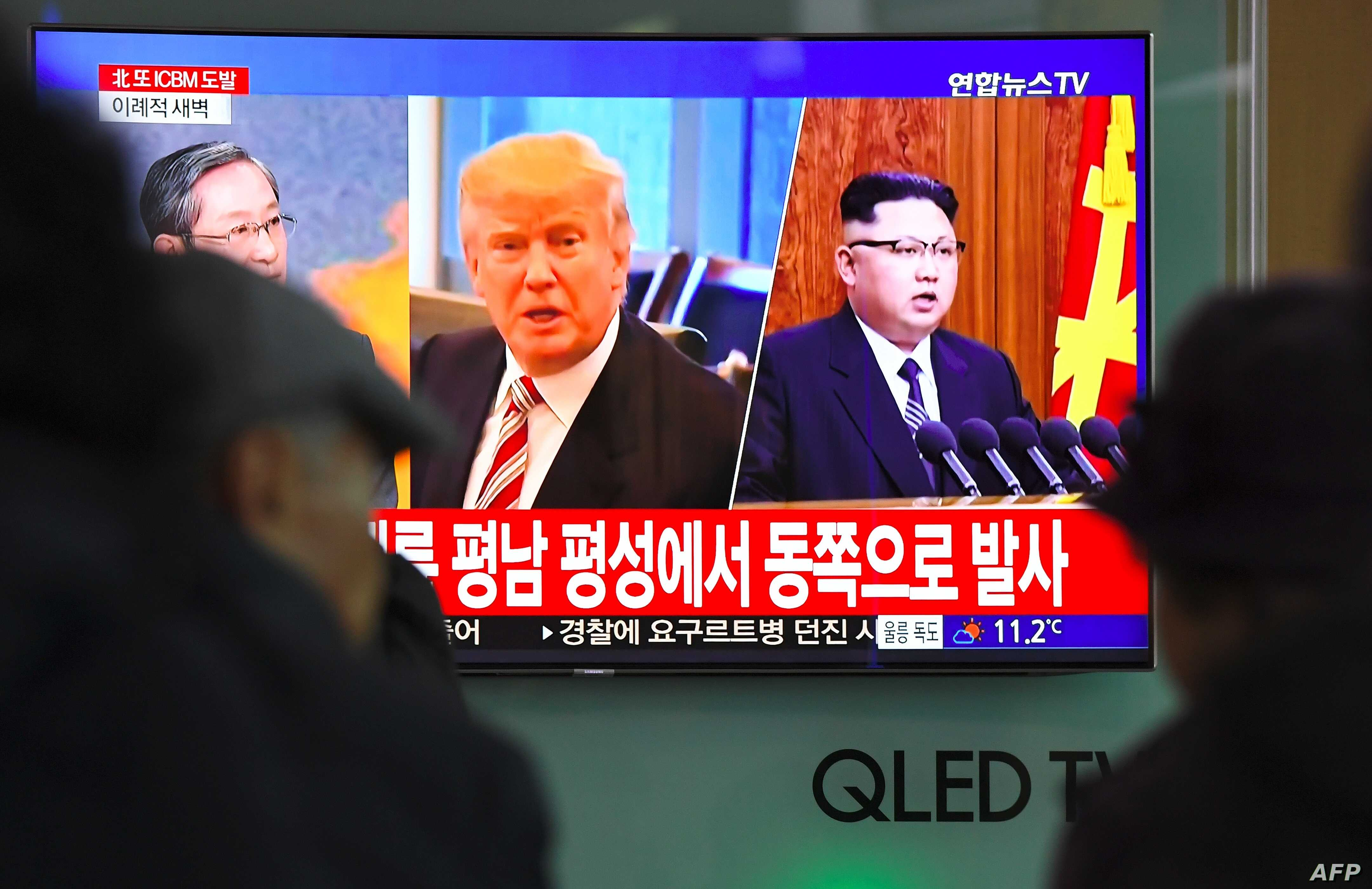 People watch a television news screen showing pictures of U.S. President Donald Trump and North Korean leader Kim Jong Un at a railway station in Seoul, Nov. 29, 2017.