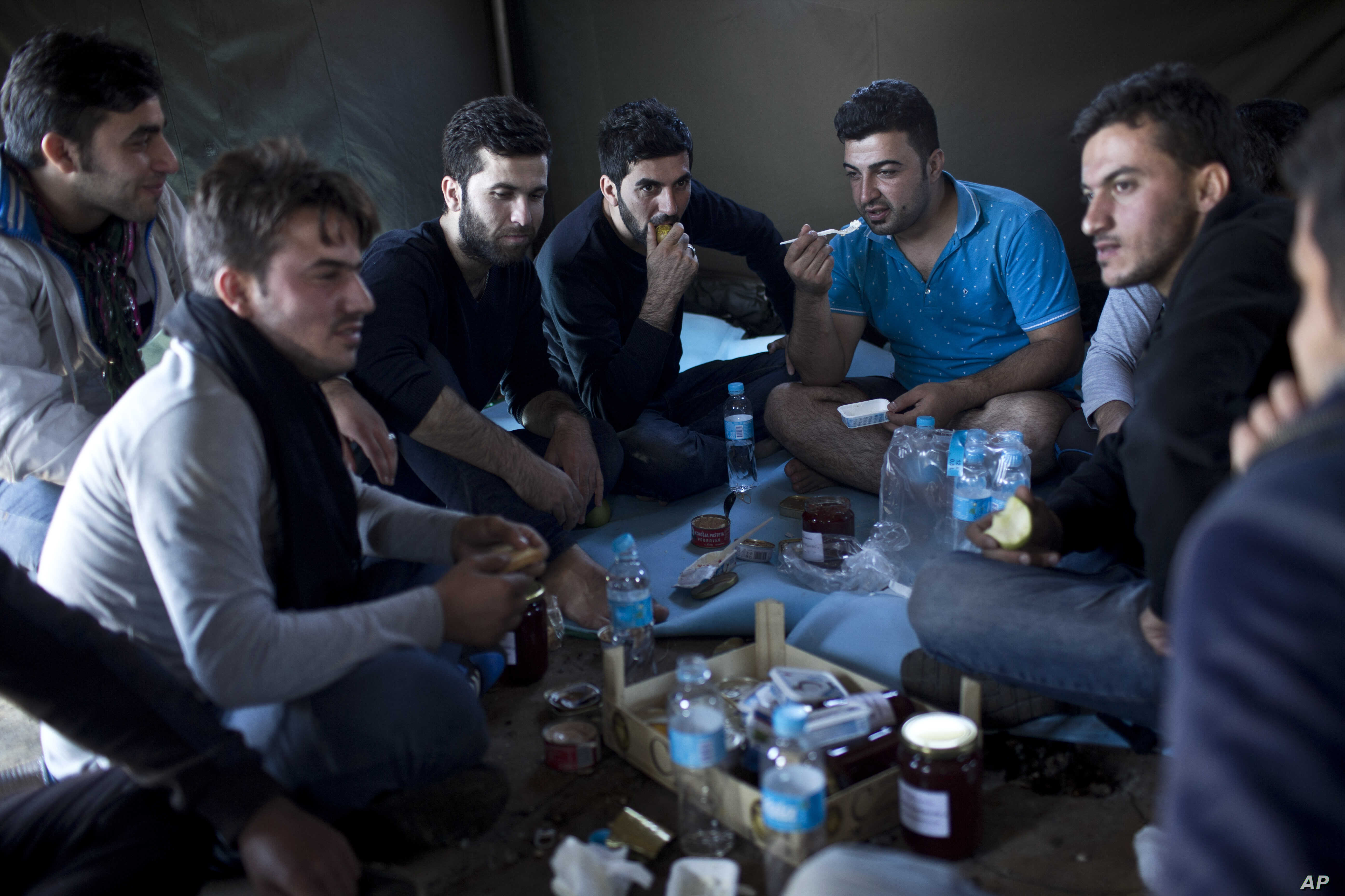 People eat a meal inside a tent at a newly established reception center for migrants and refugees close to Croatia's border with Serbia, in the town of Opatovac, Croatia, Sept. 21, 2015.