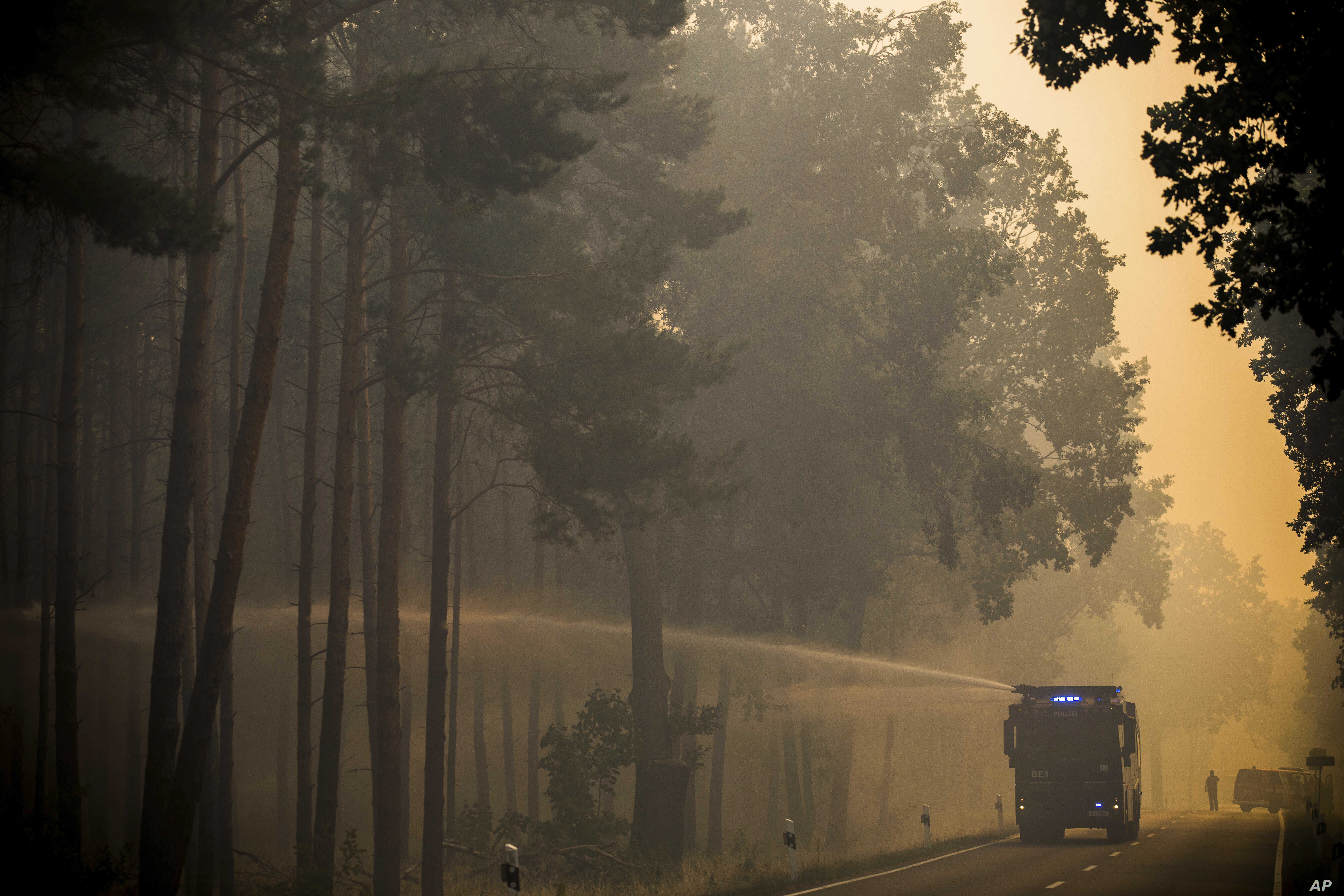 A police water cannon sprays water into a forest near Treuenbrietzen, south of Berlin,  Aug. 24, 2018 after a trees on an area of several hundred soccer fields caught fire.