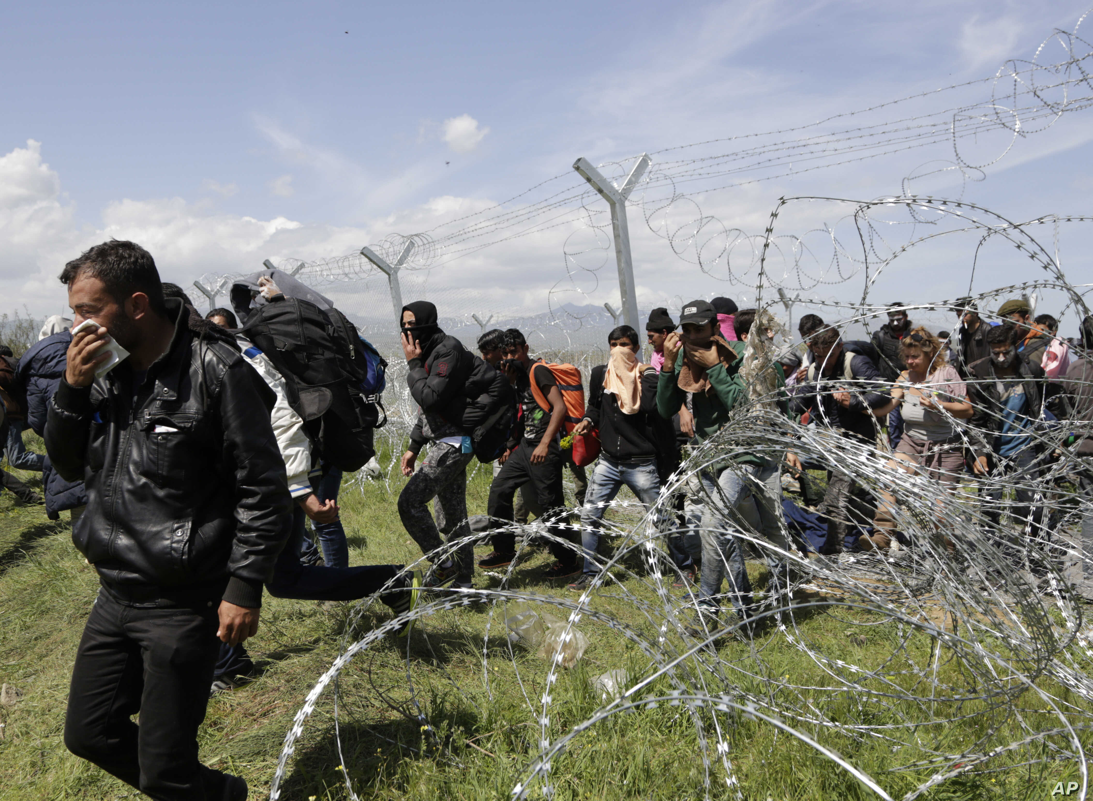 Migransts exit through a broken fence after a protest at the northern Greek border point of Idomeni, Greece, April 10, 2016.