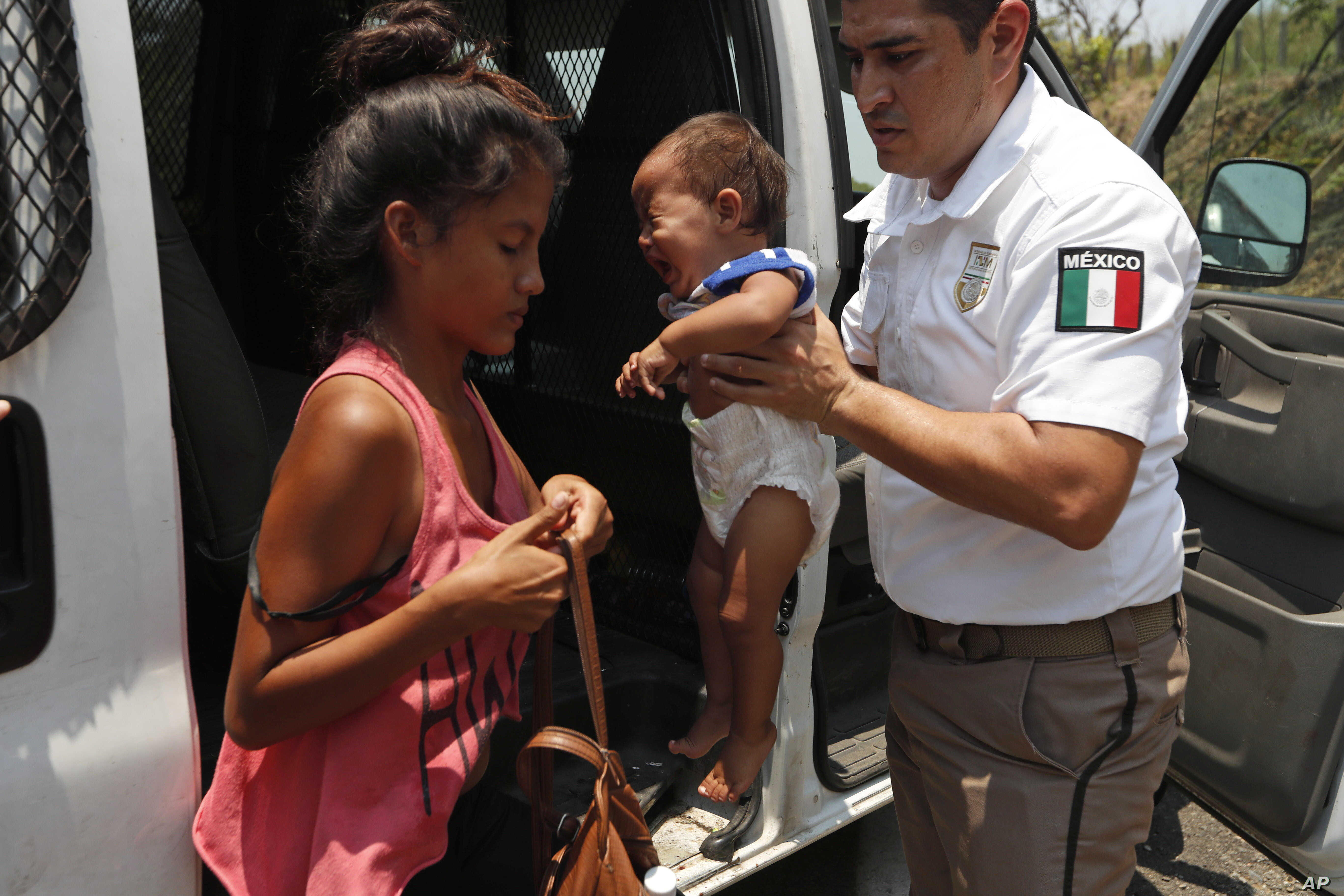 A Mexican immigration agent holds a woman's baby as she adjusts her bag so she can get into the agent's vehicle as he takes them and other Central American migrants into custody on the highway to Pijijiapan, Mexico, April 22, 2019.