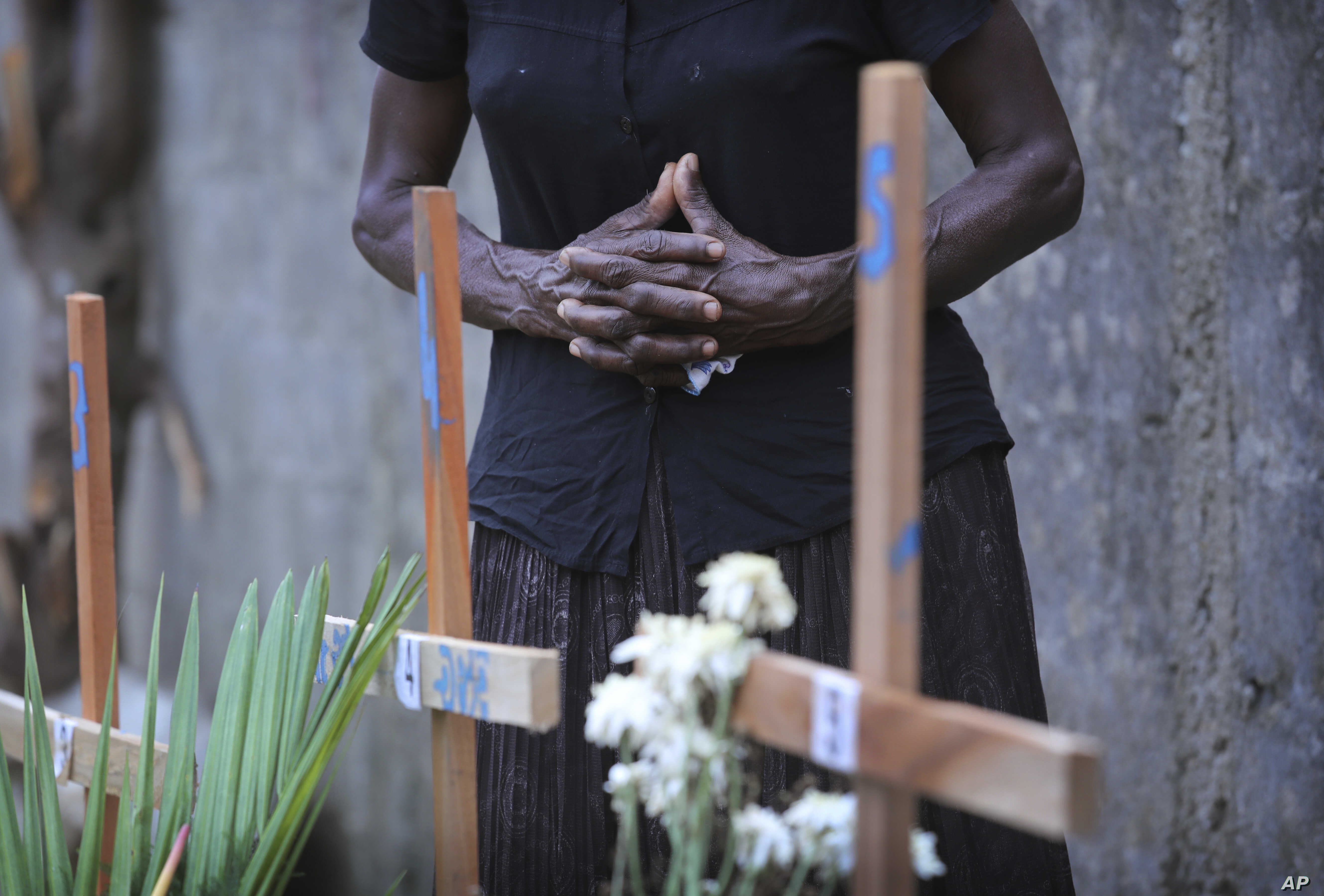 FILE - A Sri Lankan relative of a victim of Easter Sunday bomb blasts pays tribute at the burial site after a televised Sunday Mass by Sri Lankan Archbishop Cardinal Malcolm Ranjith, in Negombo, north of Colombo, Sri Lanka, April 28, 2019. Sri Lankan...
