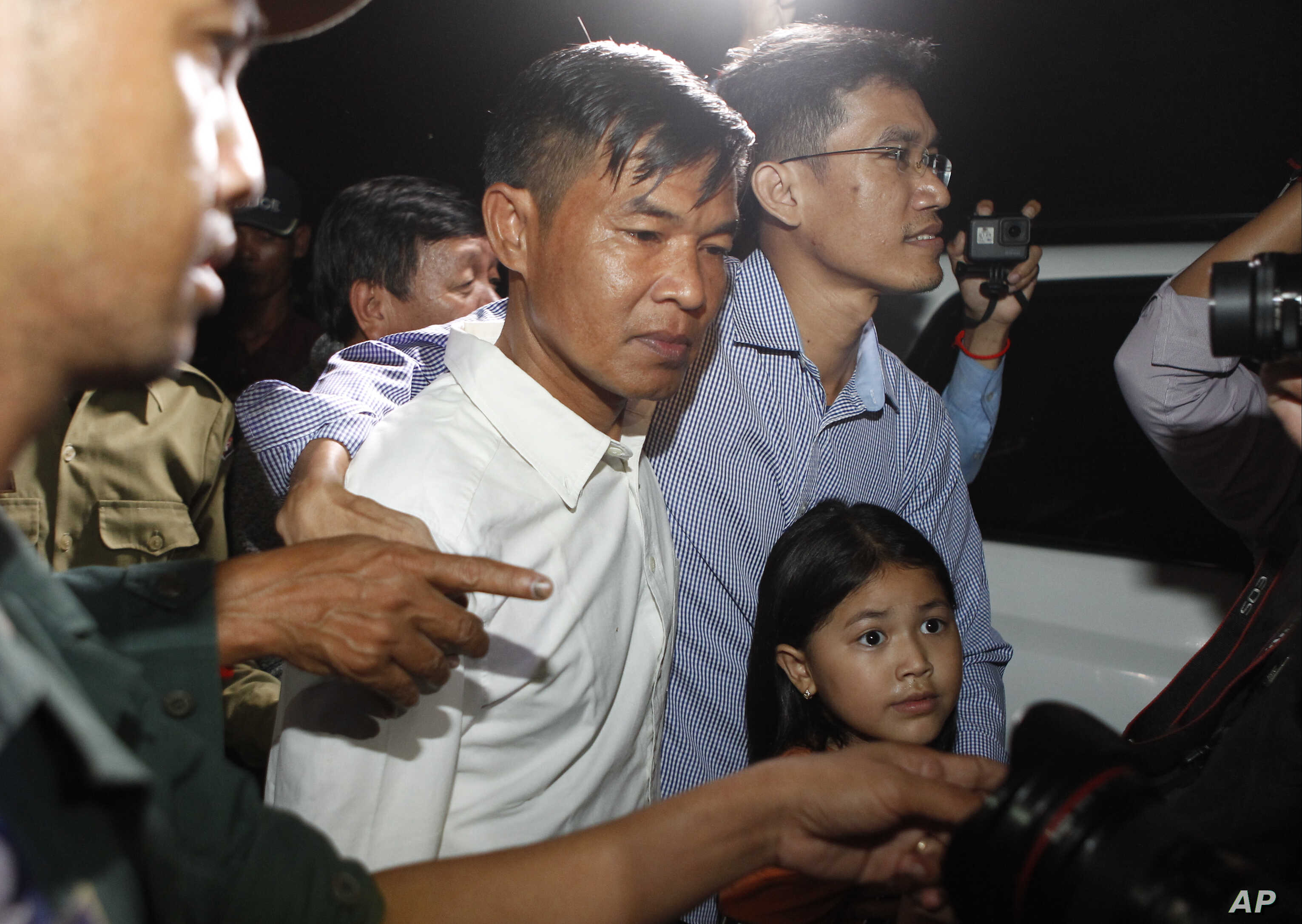FILE - Two former Radio Free Asia reporters Uon Chhin, center, and Yeang Socheamet, right, hold together as they walk outside the main prison of Prey Sar at the outskirt of Phnom Penh, Cambodia, Aug. 21, 2018.