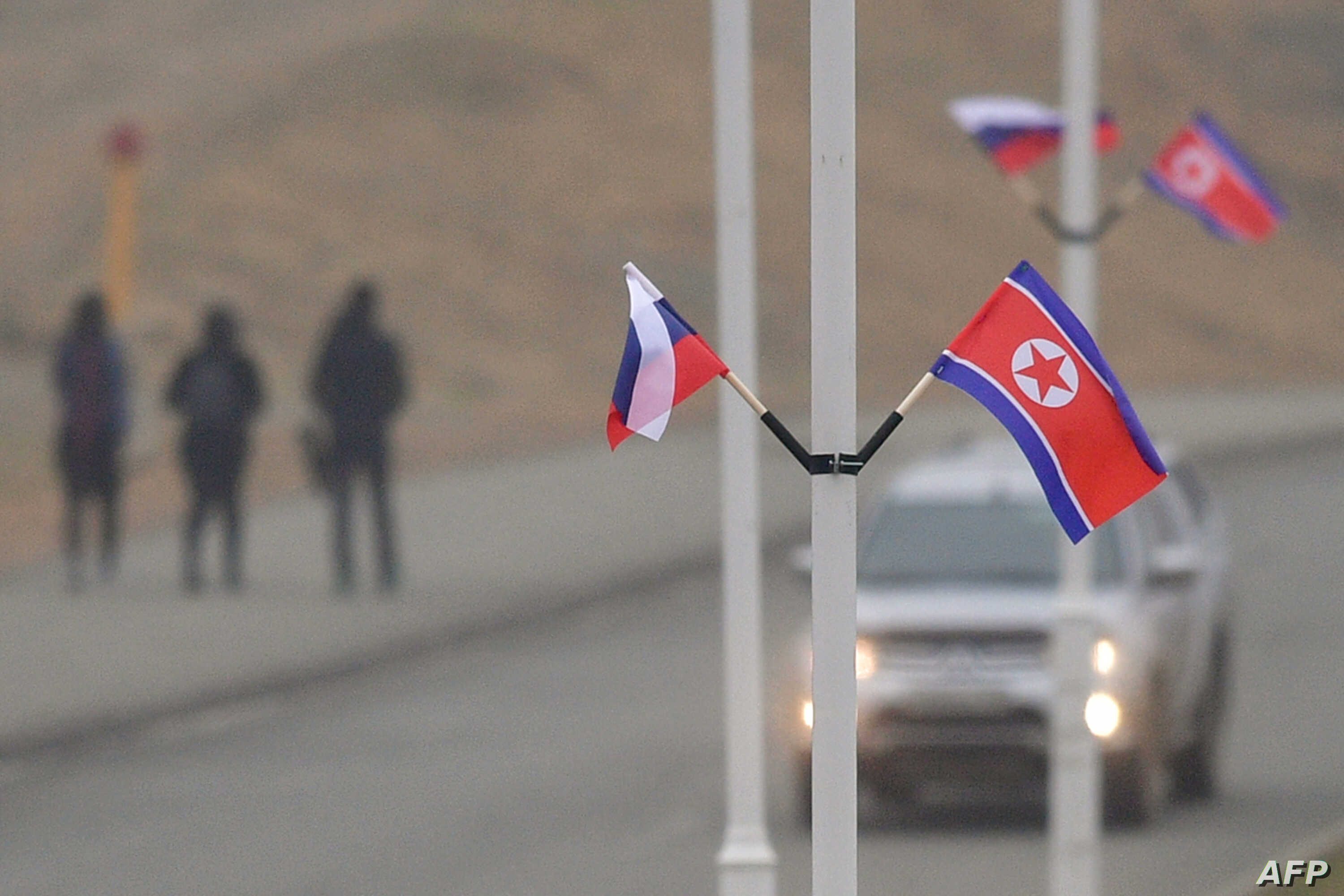 Flags of Russia and North Korea are seen fixed on lamp posts on Russky island in the far-eastern Russian port of Vladivostok on April 23, 2019.