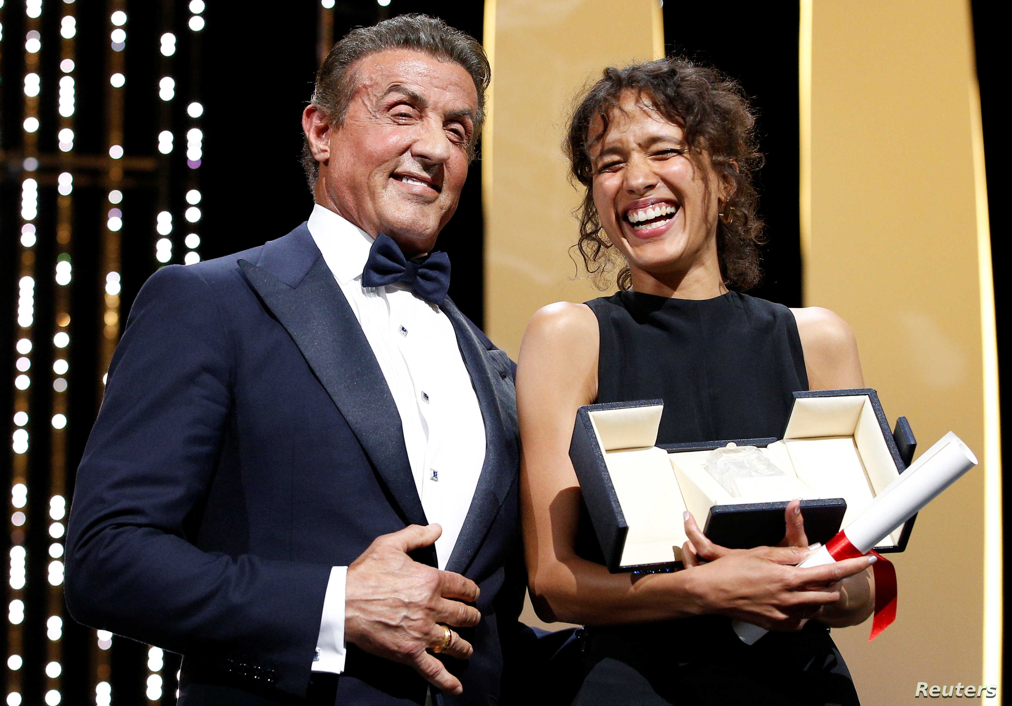 "Director Mati Diop, Grand Prix award winner for her film ""Atlantics,"" reacts next to Sylvester Stallone at the 72nd Cannes Film Festival in Cannes, France, May 25, 2019."