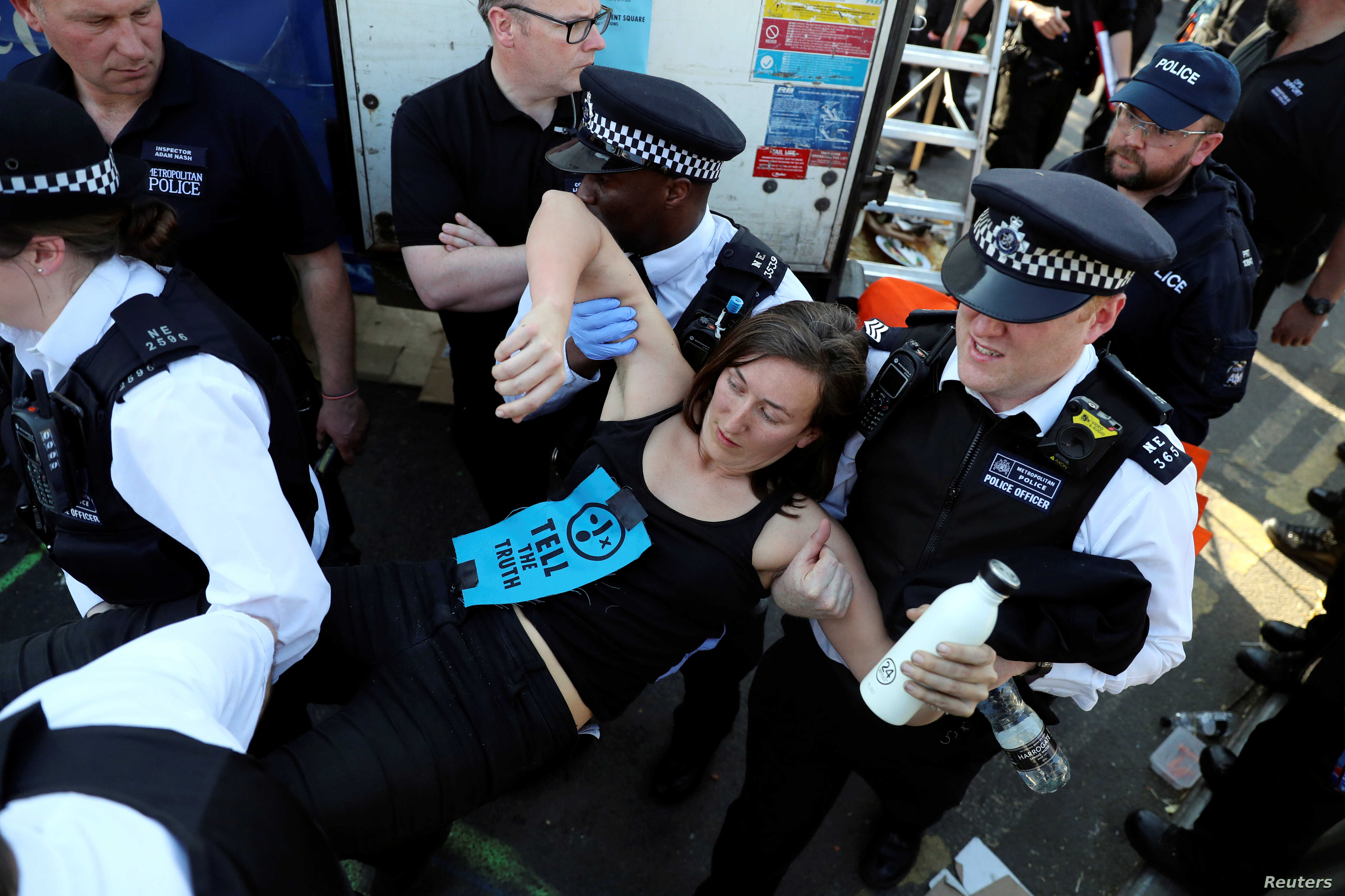 A climate change activist is detained during the Extinction Rebellion protest on Waterloo Bridge in London, Britain, April 20, 2019.
