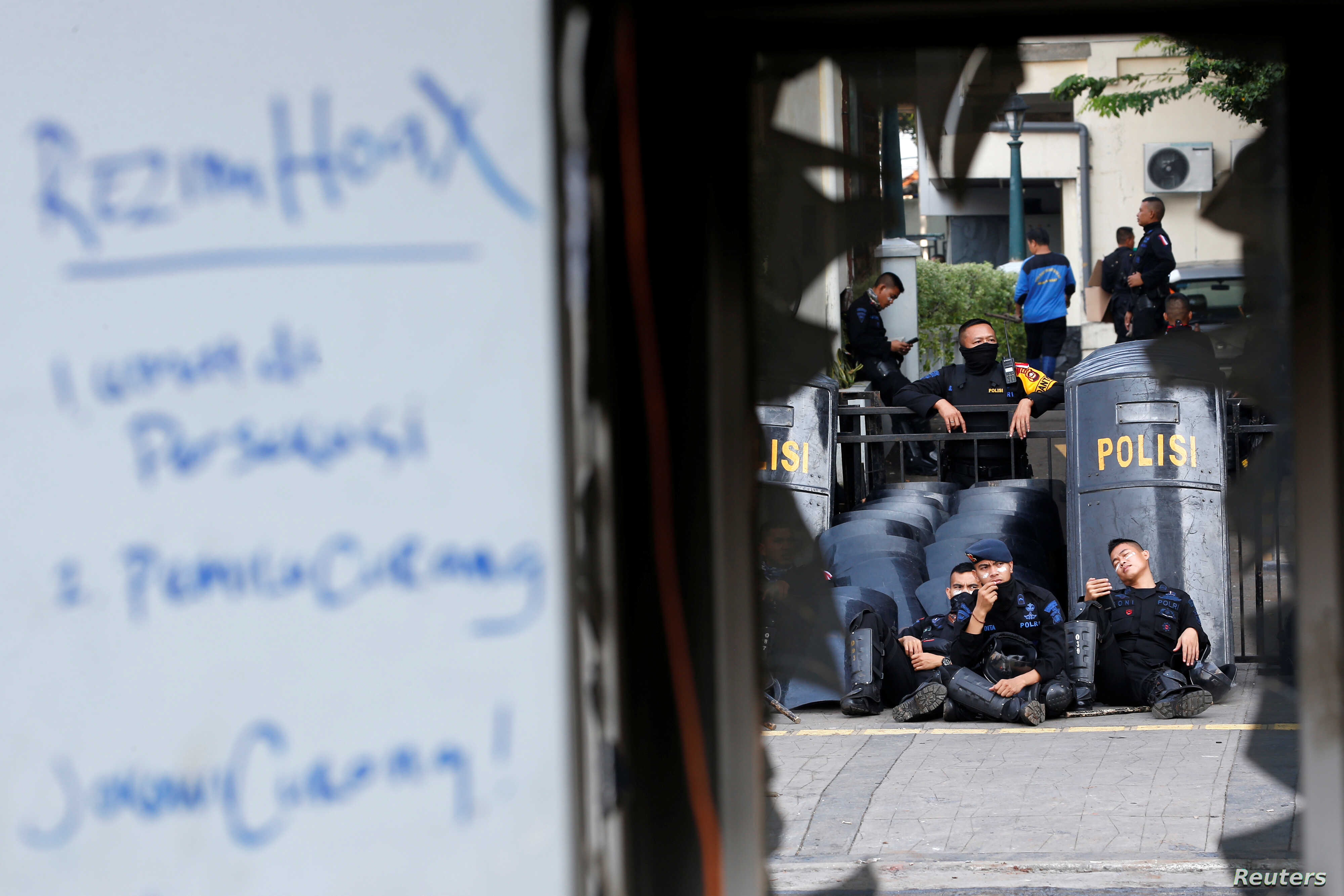 Mobile brigade (Brimob) police officers take a rest near a damaged police station after riots following the announcement of last month's presidential election results outside the Election Supervisory Agency (Bawaslu) headquarters in Jakarta, Indonesi...
