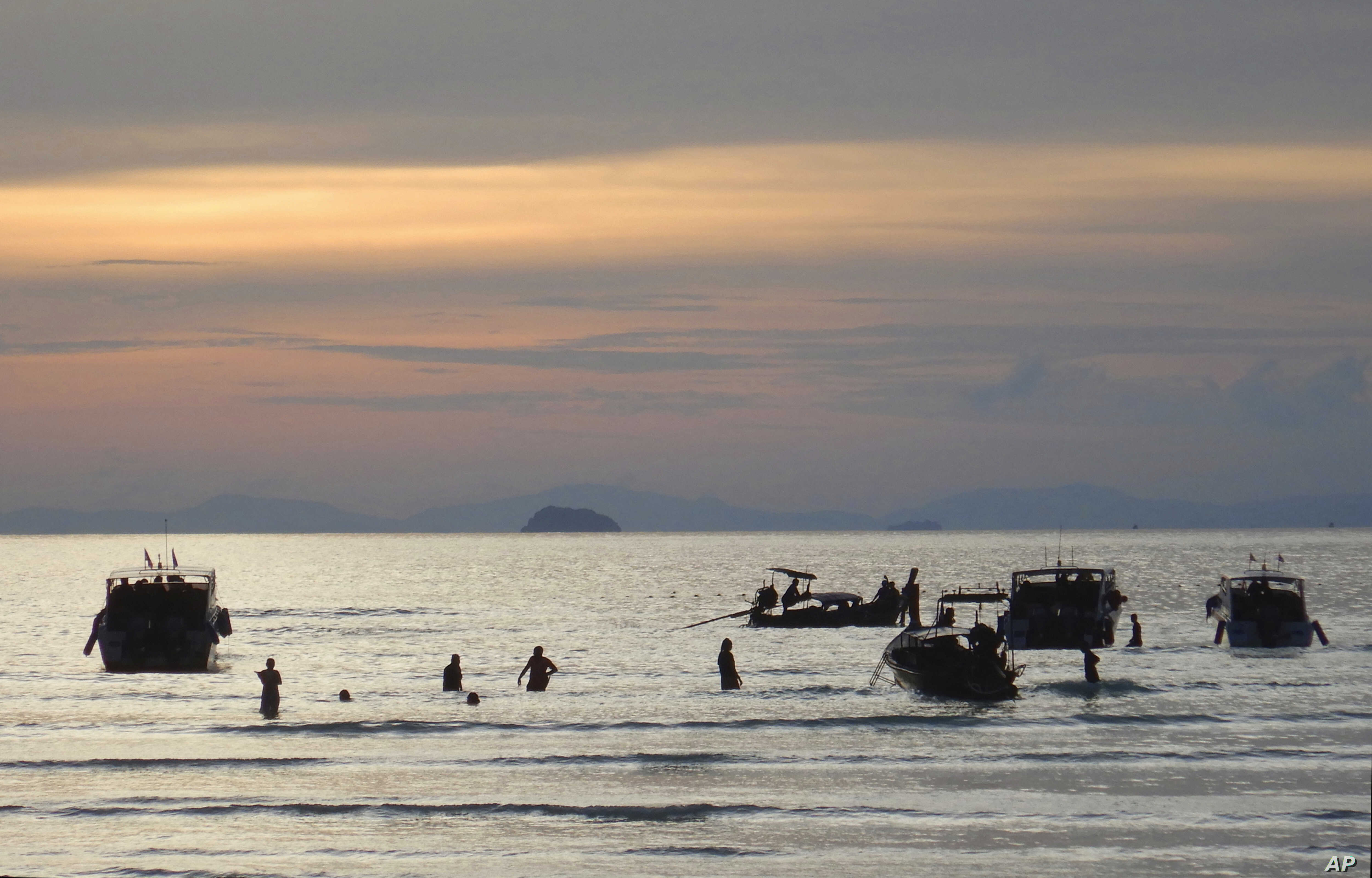Tourists wade in the shallow water back to their boats from Maya Bay on Phi Phi Leh island, Krabi province, Thailand, May 31, 2018.