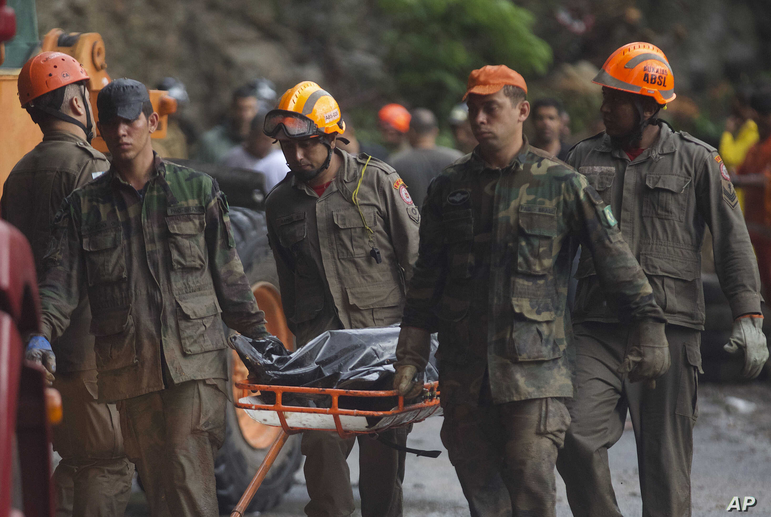 Firefighters and soldiers remove a body recovered from an area where heavy rains caused a mudslide half-burying several vehicles and uprooting trees, in Rio de Janeiro, Brazil, April 9, 2019.