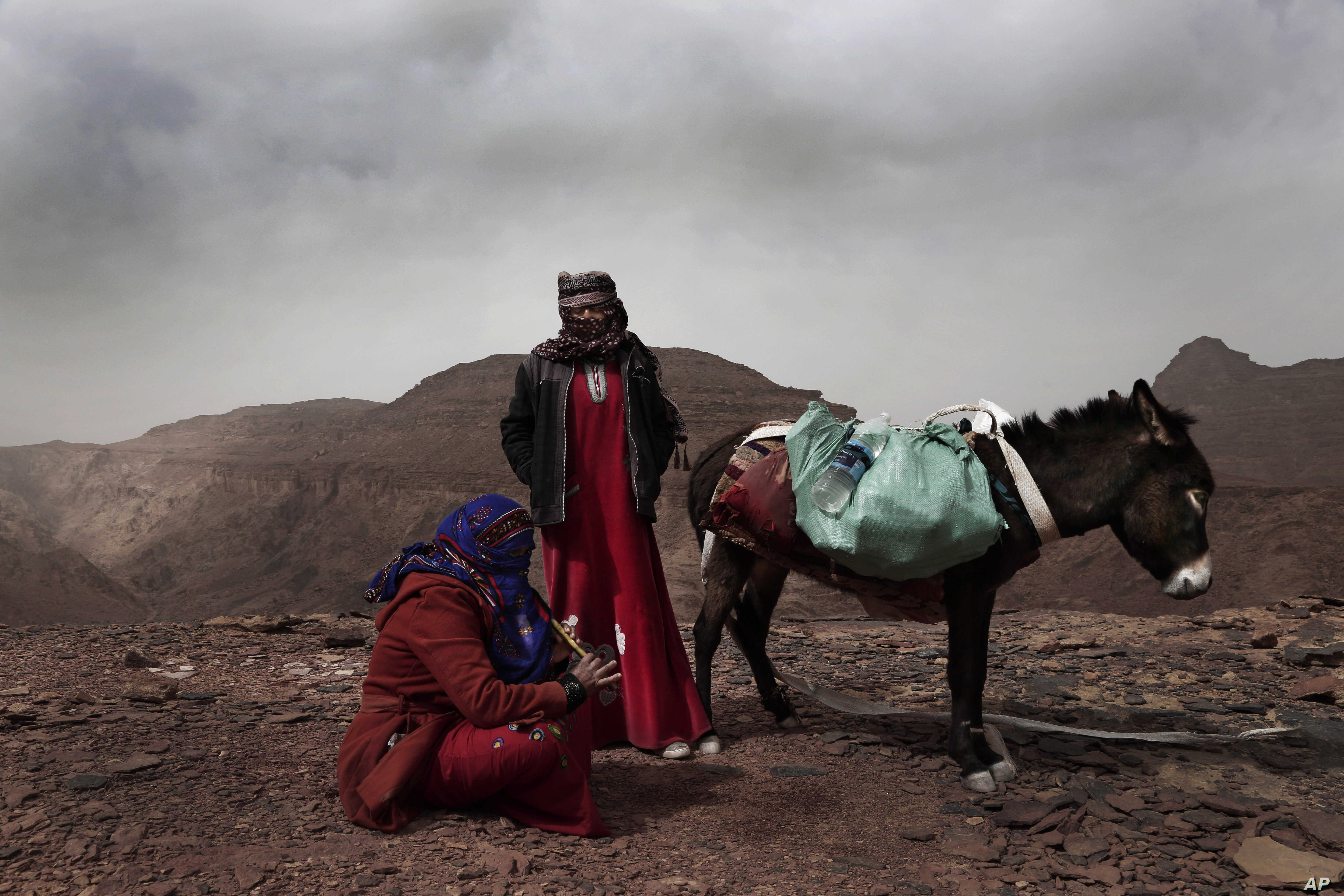 Umm Yasser, the first Bedouin female guide from the Hamada tribe, looks at Umm Soliman as she plays the flute, near Wadi Sahw, Abu Zenima, in South Sinai, Egypt, March 30, 2019.