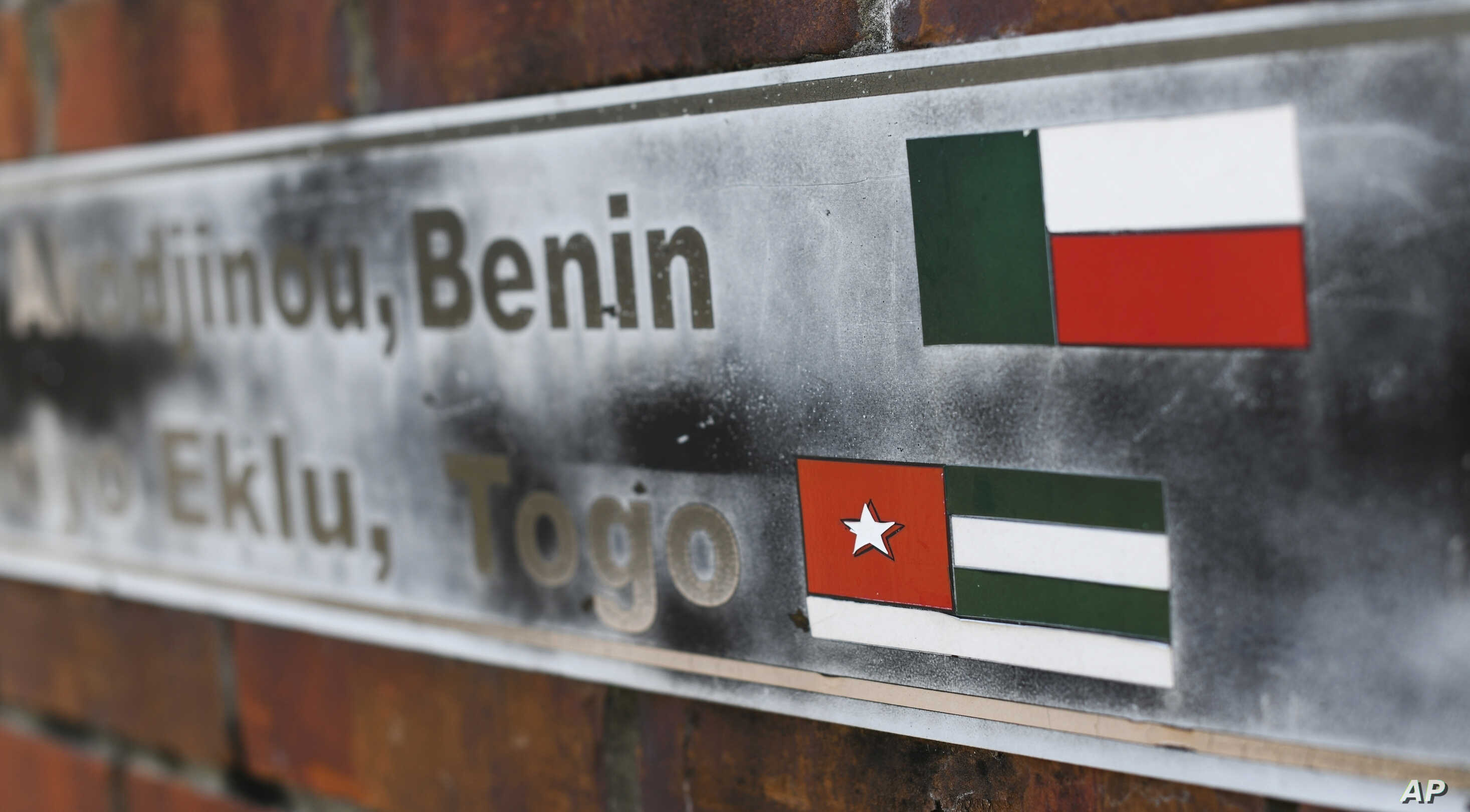 FILE - The flags of the nations of Benin and Togo, the west African homes of the survivors of the slave ship Clotilda, remain on display on a monument at what was the Africatown Welcome Center in Mobile, Ala., Jan. 29, 2019. The center was destroyed ...