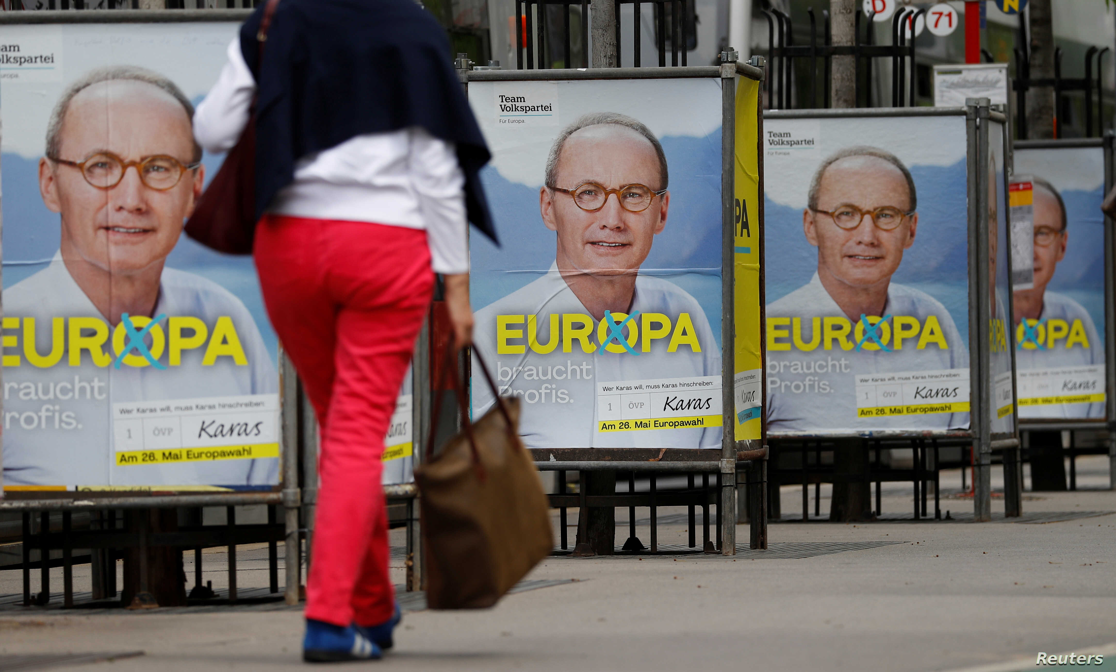A woman walks past European election posters of the top candidate of Austria's Peoples Party OeVP for the EU elections Othmar Karas in Vienna, Austria, April 26, 2019.