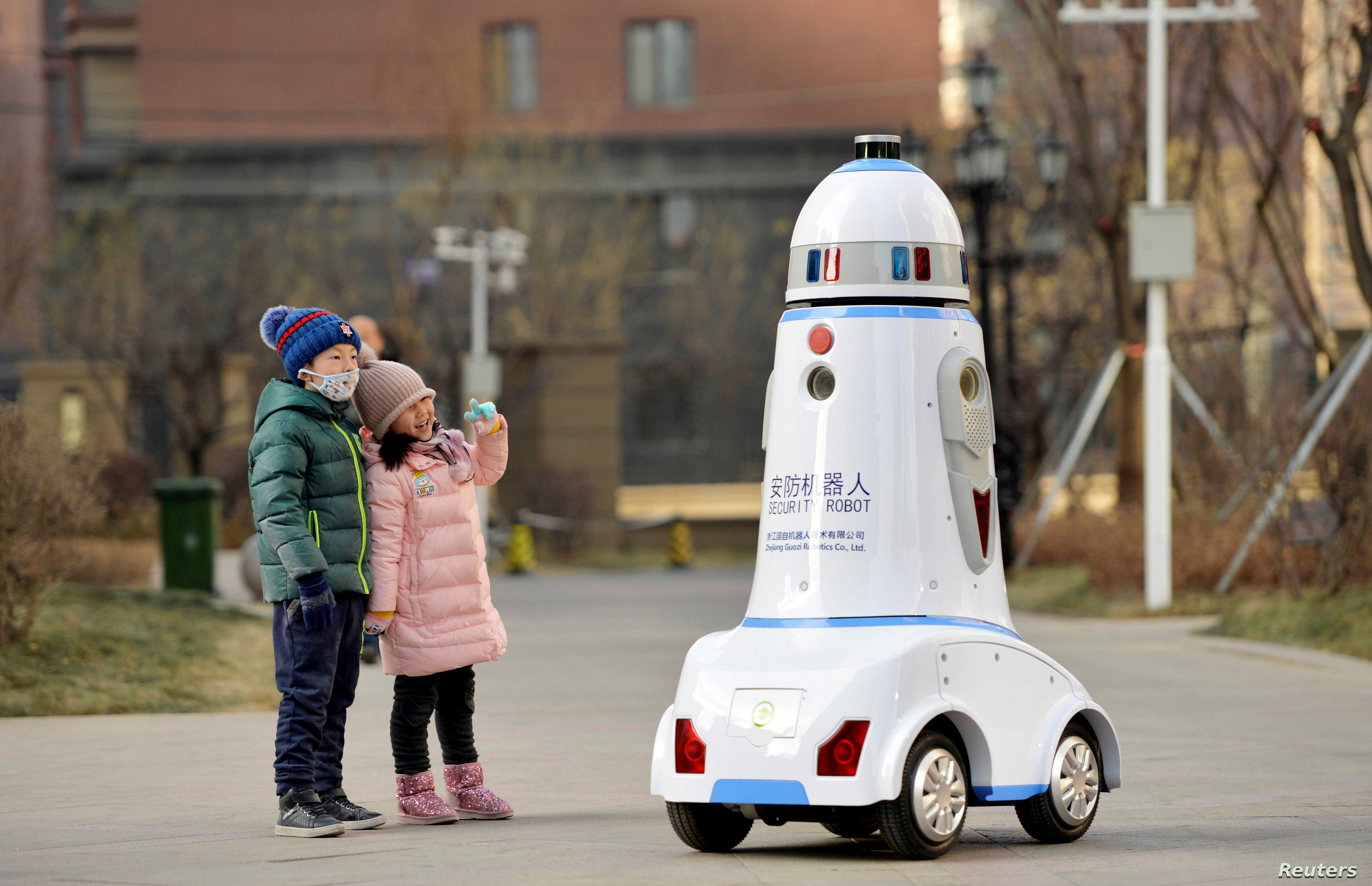 FILE - Children react next to a security robot patroling inside a residential compound in Hohhot, Inner Mongolia, China, Jan. 18, 2019.
