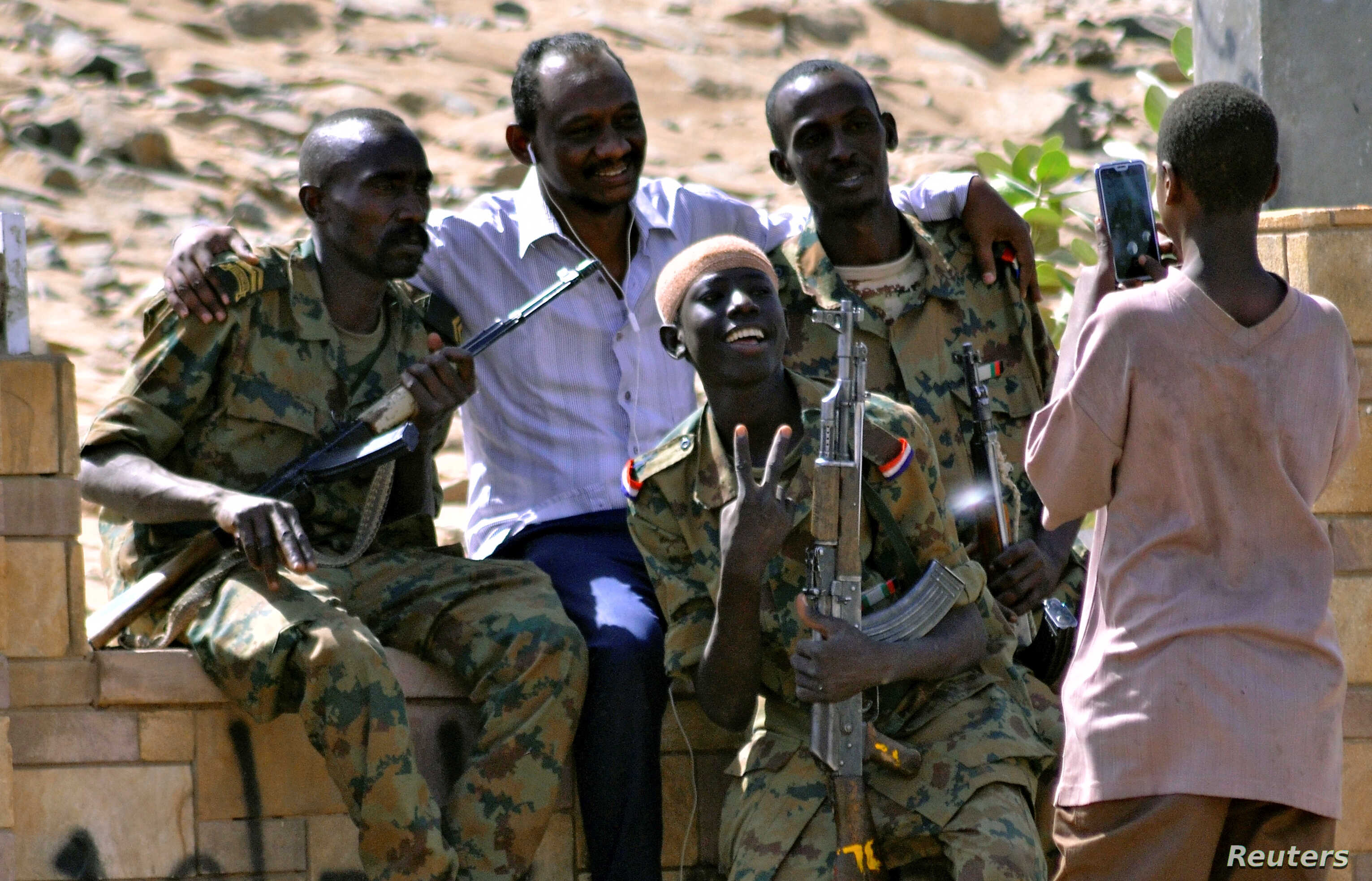 Sudanese military officers and a demonstrator pose for a photograph during celebration after Defense Minister Awad Ibn Auf stepped down as head of the country's transitional ruling military council, near the Defense Ministry in Khartoum, Sudan, April...