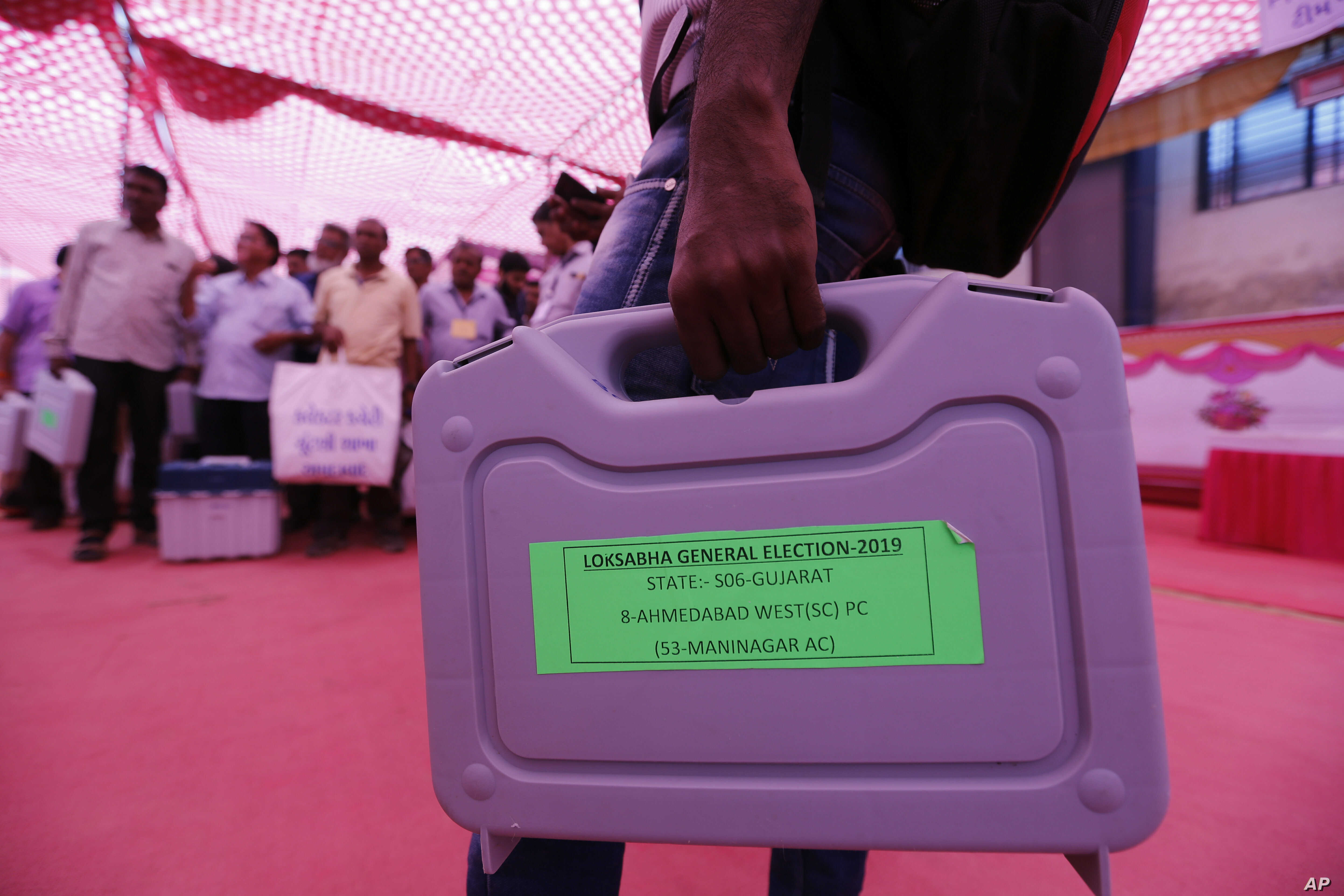 Officials on election duty carry electronic voting machines ahead of the general election in Ahmadabad, India, April 22, 2019.