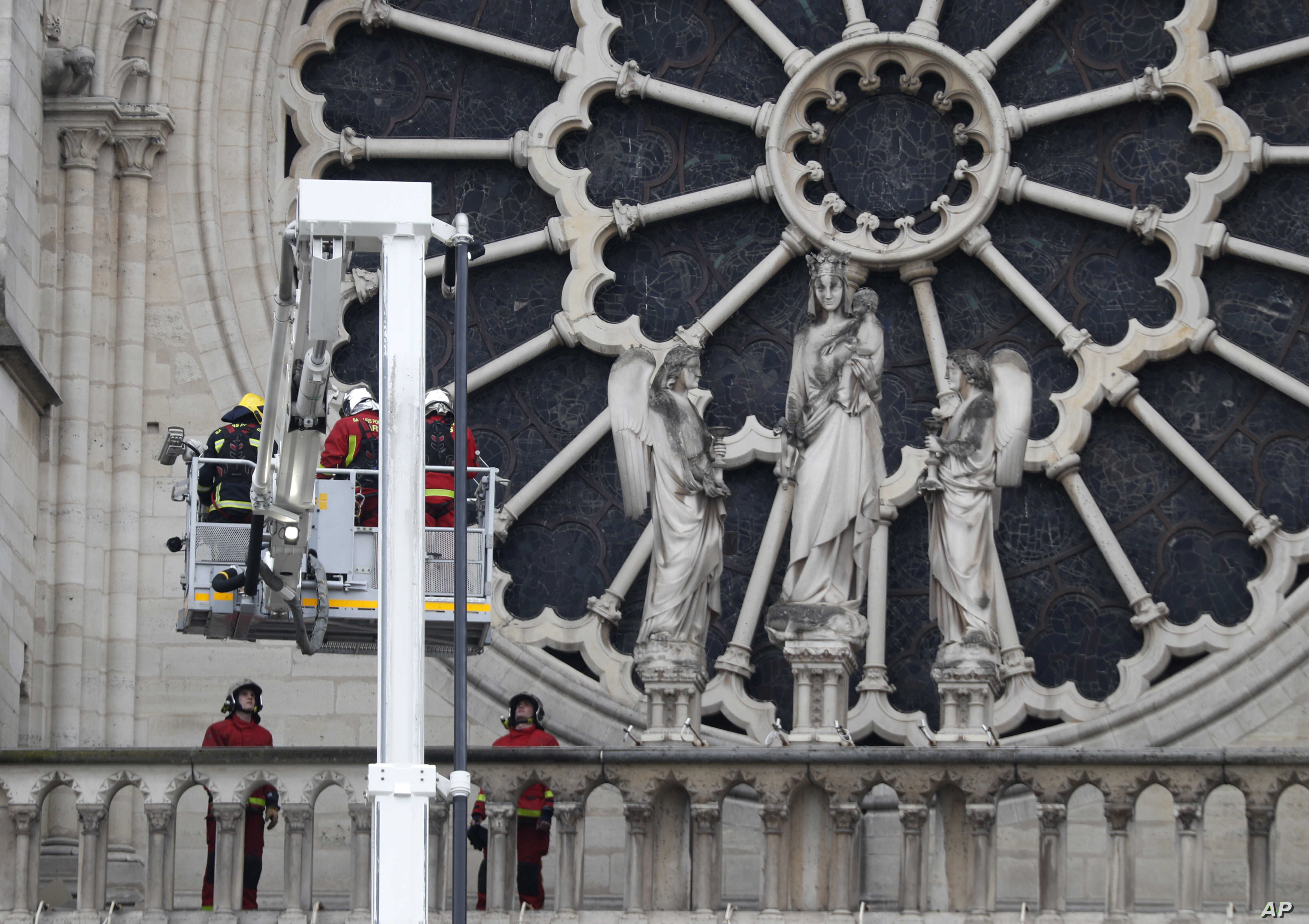 Firefighters work near the rose window of Notre Dame cathedral, Apr. 16, 2019 in Paris.