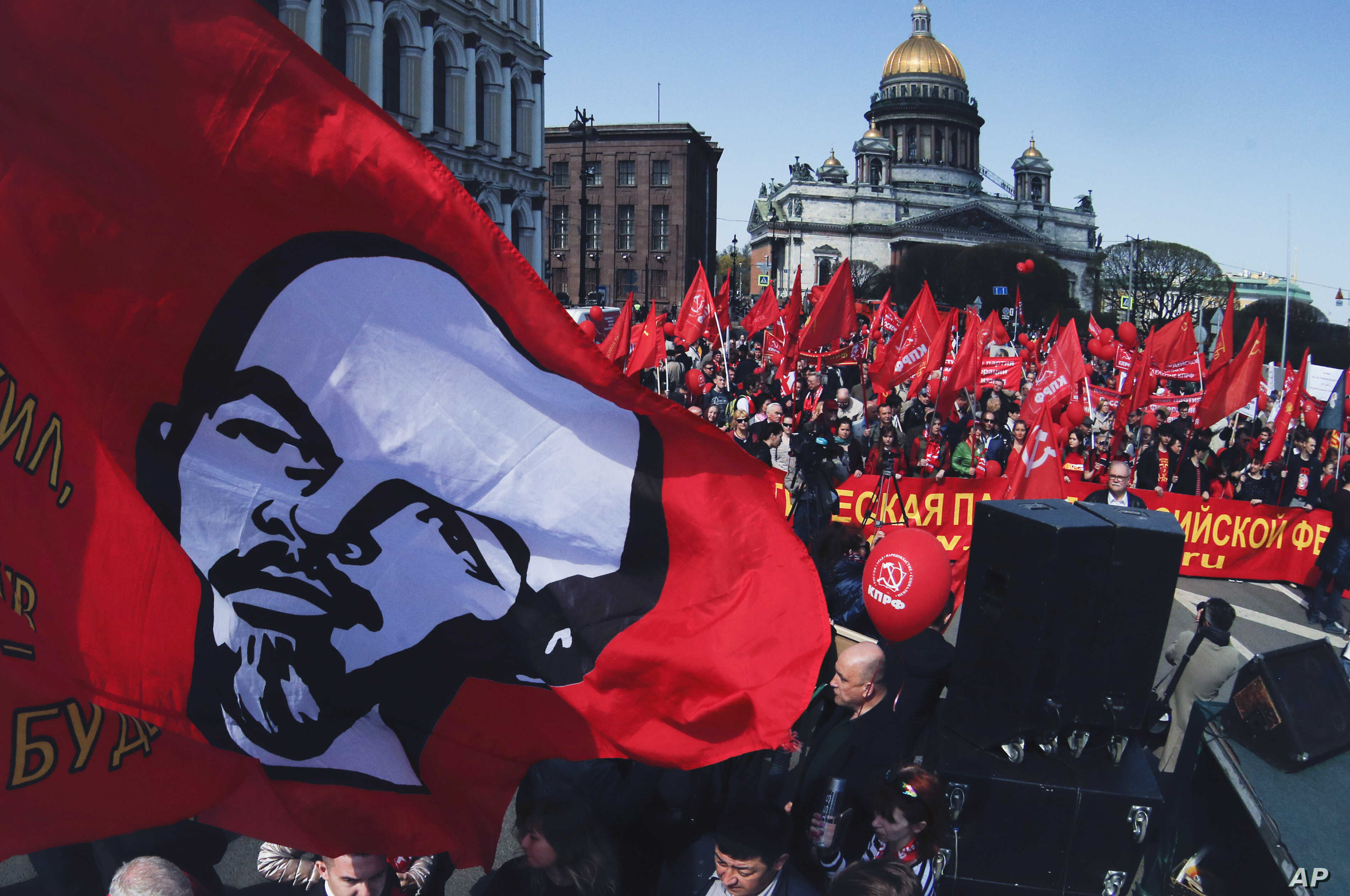 Communist party supporters carry a flag depicting Soviet Union founder Lenin during a May Day rally in St.Petersburg, Russia, May 1, 2019.