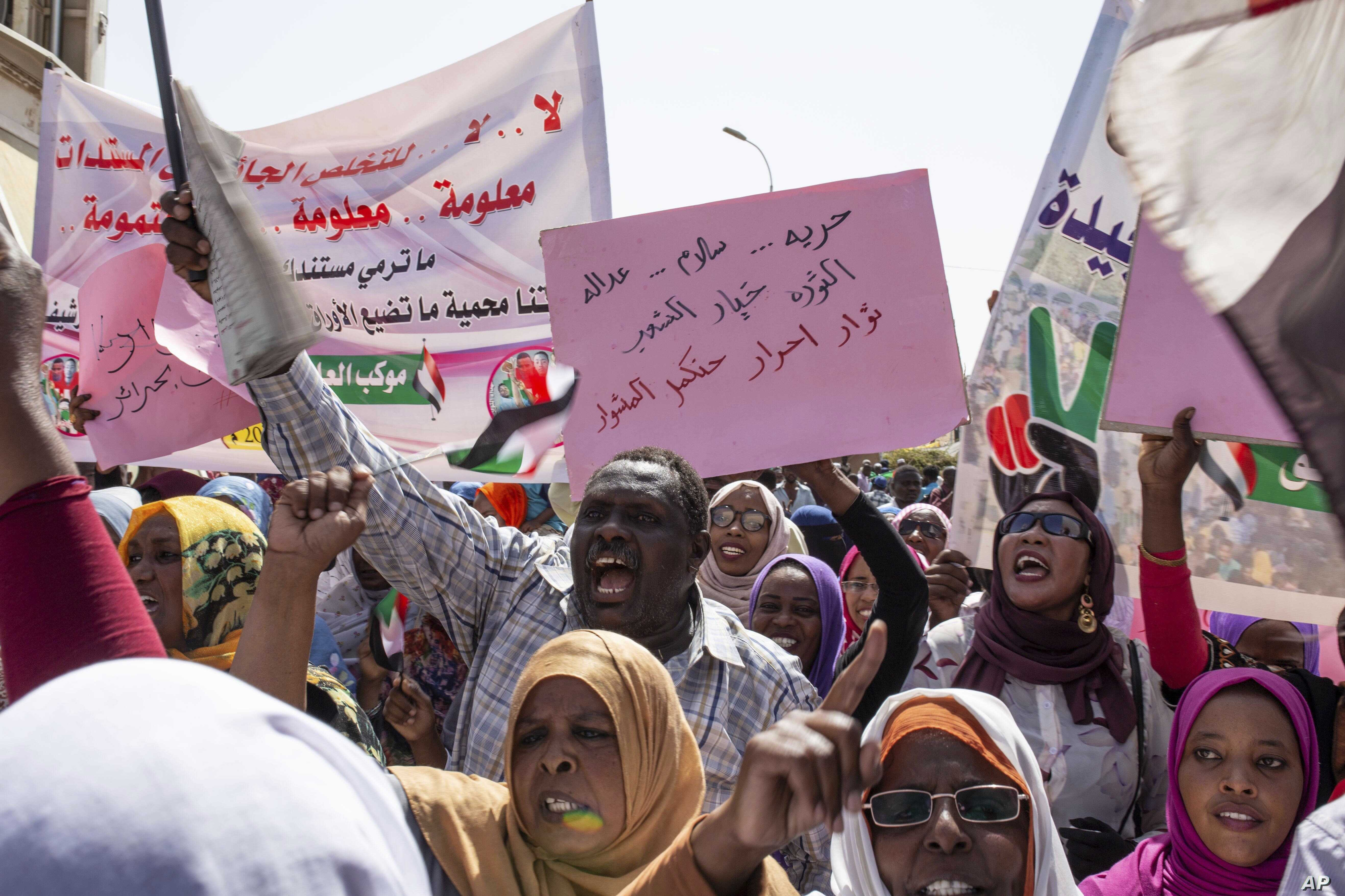 """Protesters carry posters in Arabic that say, """"Freedom, justice, and peace, and the revolution is the choice of the people,"""" at the sit-in outside the military headquarters, in Khartoum, Sudan, May 2, 2019."""